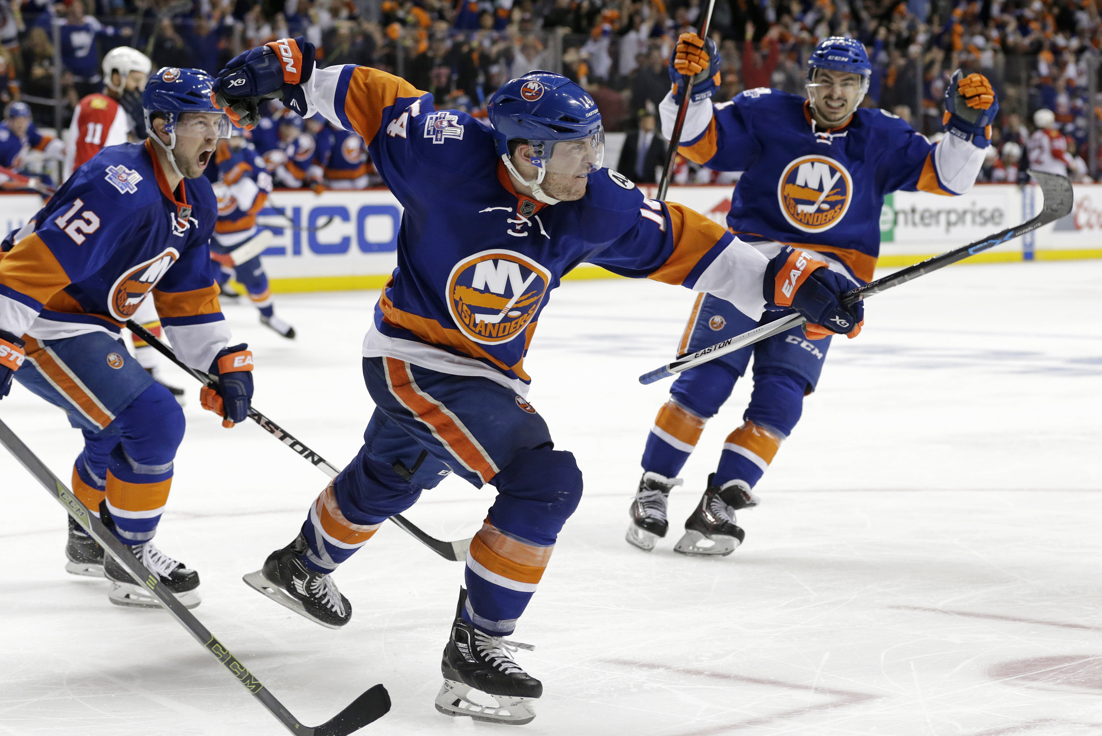 New York Islanders defenseman Thomas Hickey (14) celebrates after scoring the game-winning goal during overtime in Game 3 of an NHL hockey first-round Stanley Cup playoff series against the Florida Panthers, Sunday, April 17, 2016, in New York. The Island