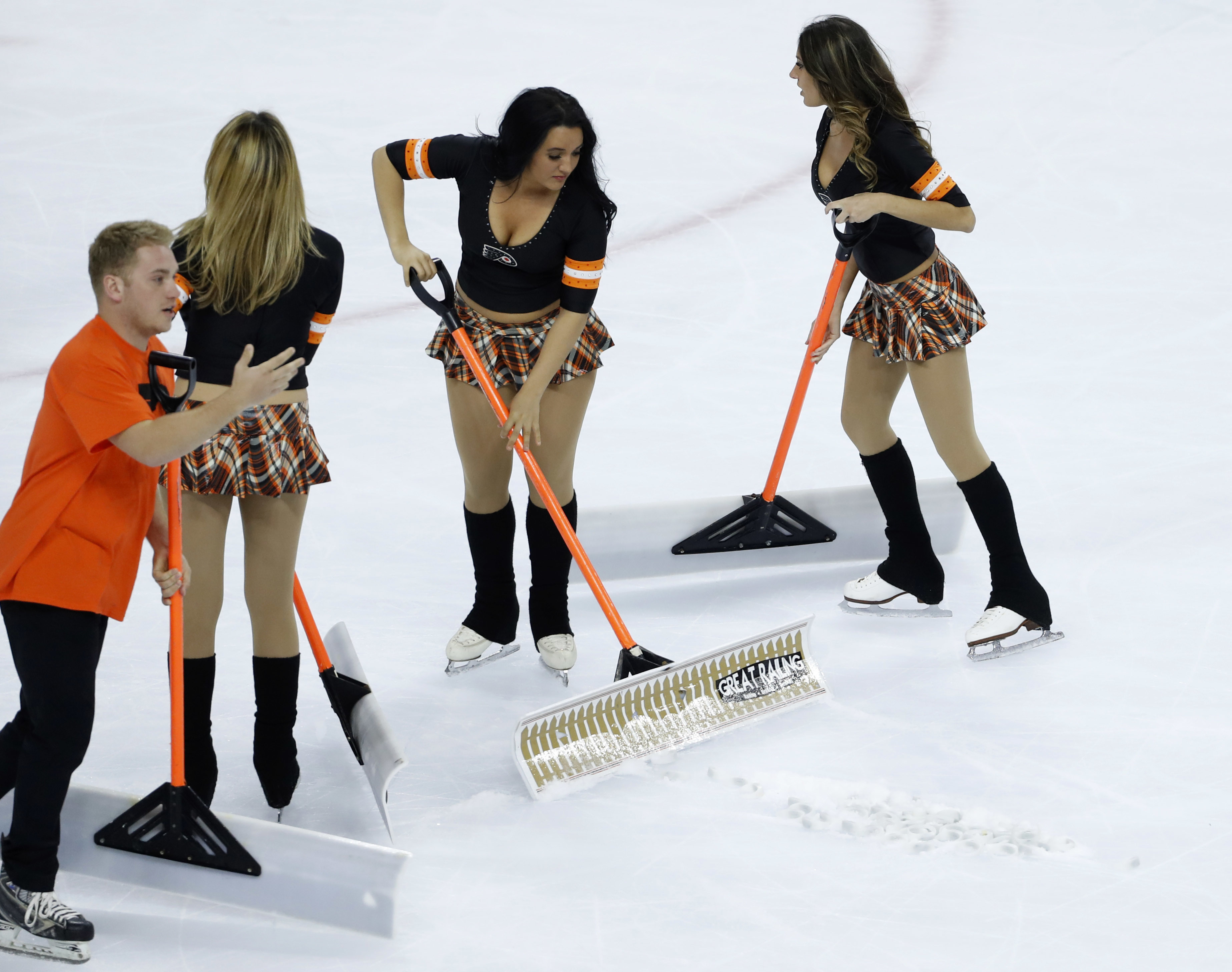Ice crew personnel clean up promotional bracelets that were thrown onto the ice during the third period of Game 3 between the Philadelphia Flyers and the Washington Capitals in the first round of the NHL Stanley Cup hockey playoffs, Monday, April 18, 2016