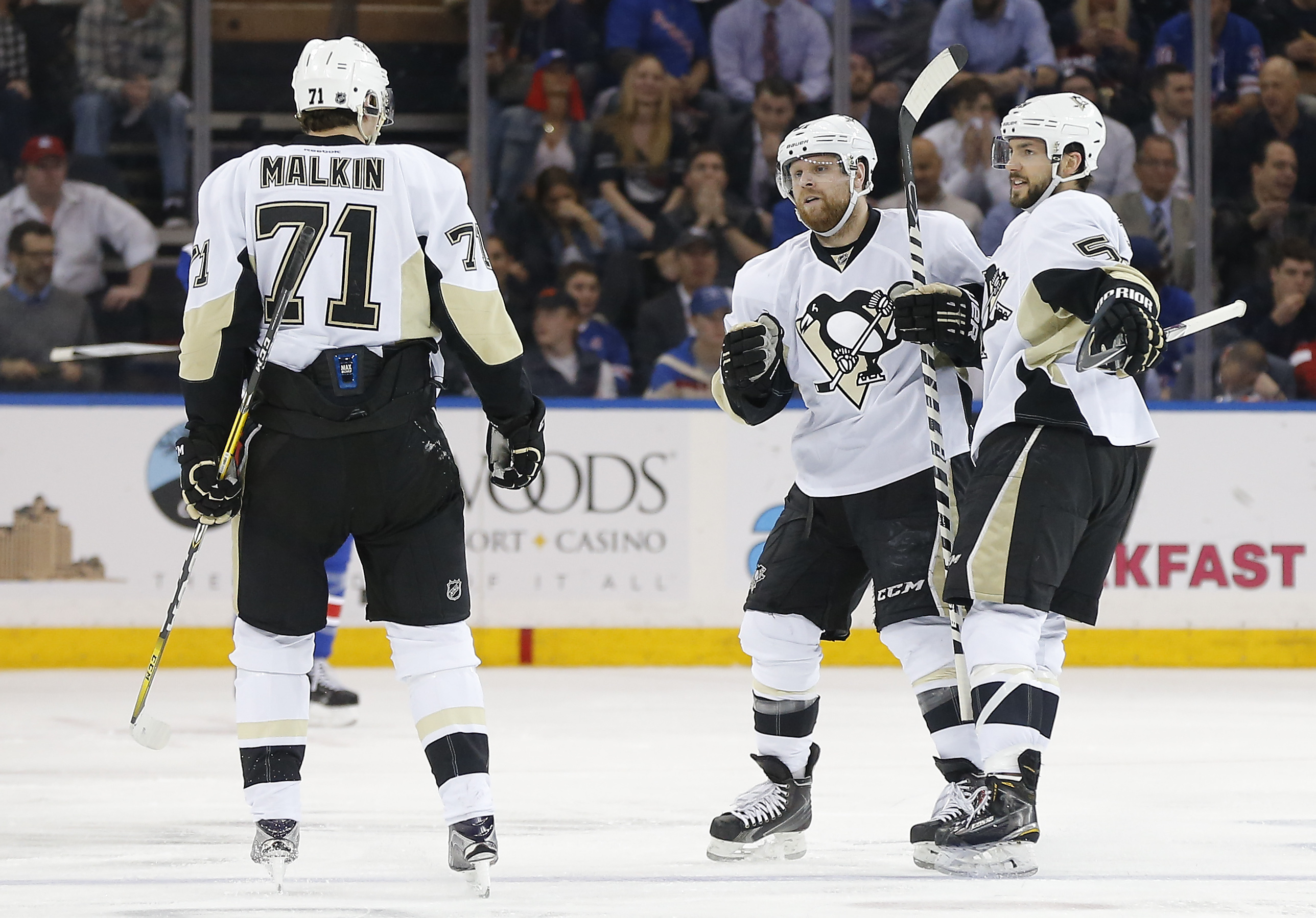 Pittsburgh Penguins defenseman Kris Letang, right, and right wing Phil Kessel, center, celebrate with center Evgeni Malkin (71) after Malkin scored a goal against the New York Rangers during the second period of Game 4 of an NHL hockey first-round Stanley