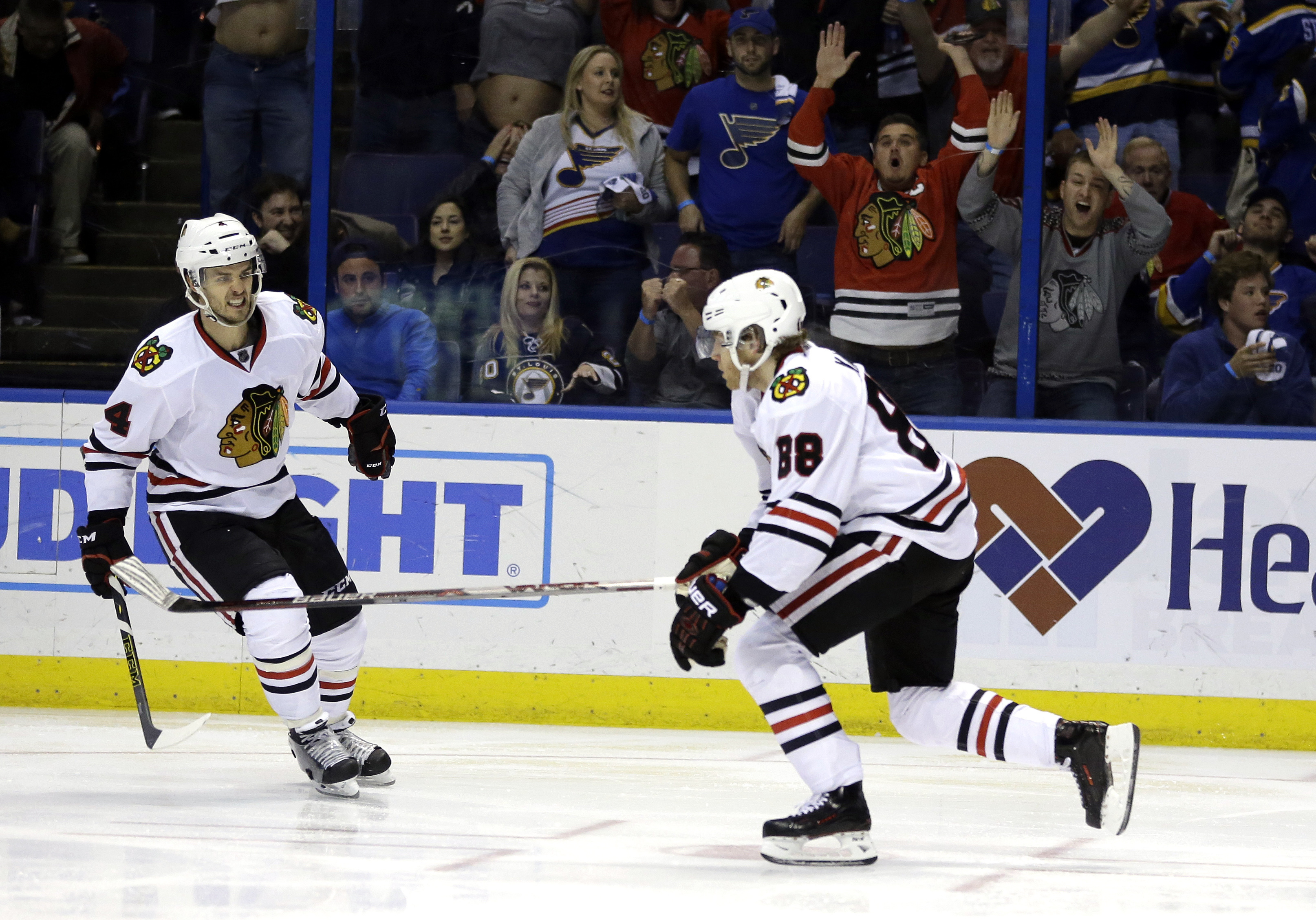 Chicago Blackhawks' Patrick Kane, right, celebrates as he skates by teammate Niklas Hjalmarsson, of Sweden, after scoring during the second overtime in Game 5 of an NHL hockey first-round Stanley Cup playoff series against the St. Louis Blues early Friday