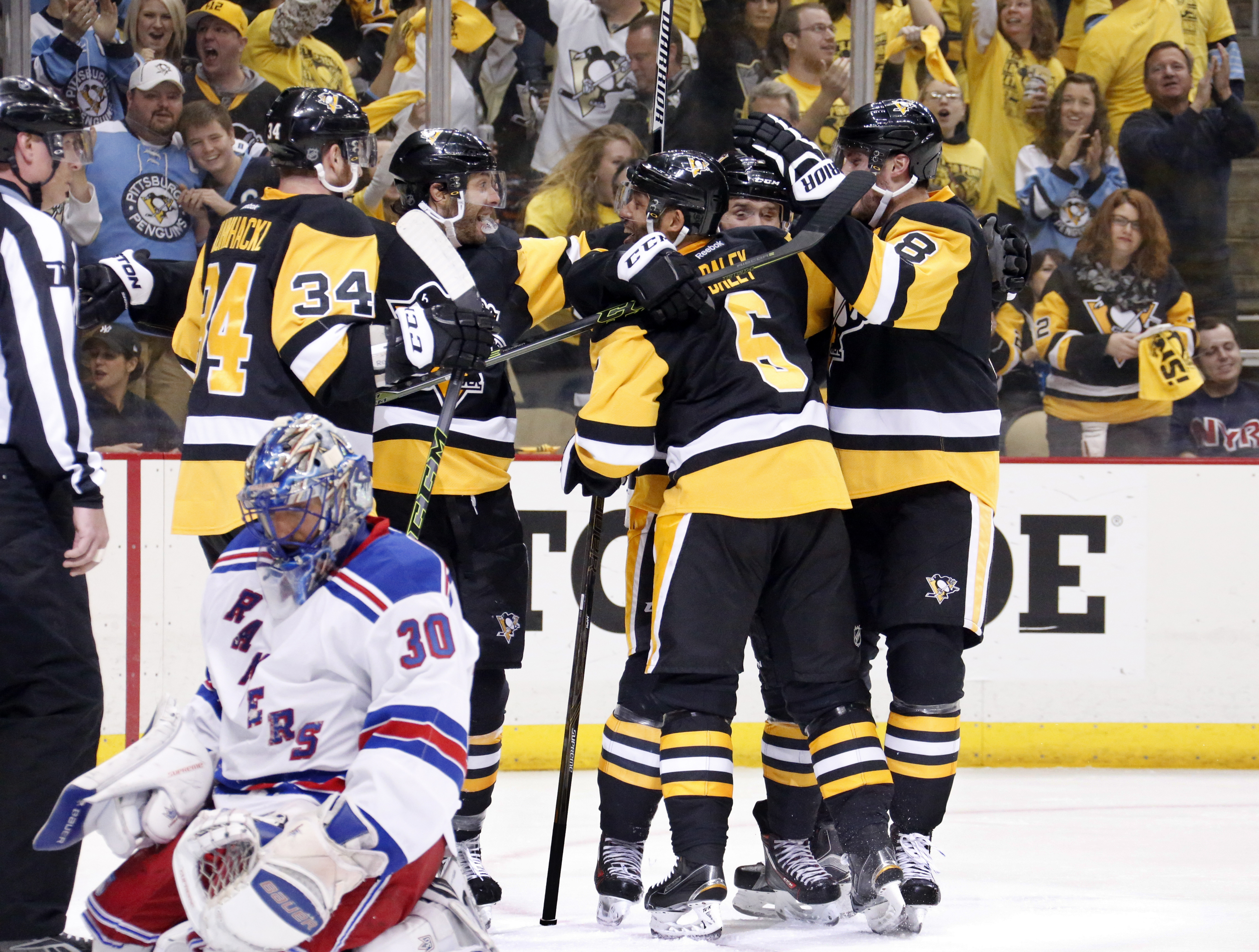 New York Rangers goalie Henrik Lundqvist (30) kneels on the ice as Pittsburgh Penguins' Bryan Rust, second from right rear, and teammates celebrate his goal during the second period in Game 5 of a first-round NHL playoff hockey game in Pittsburgh, Saturda