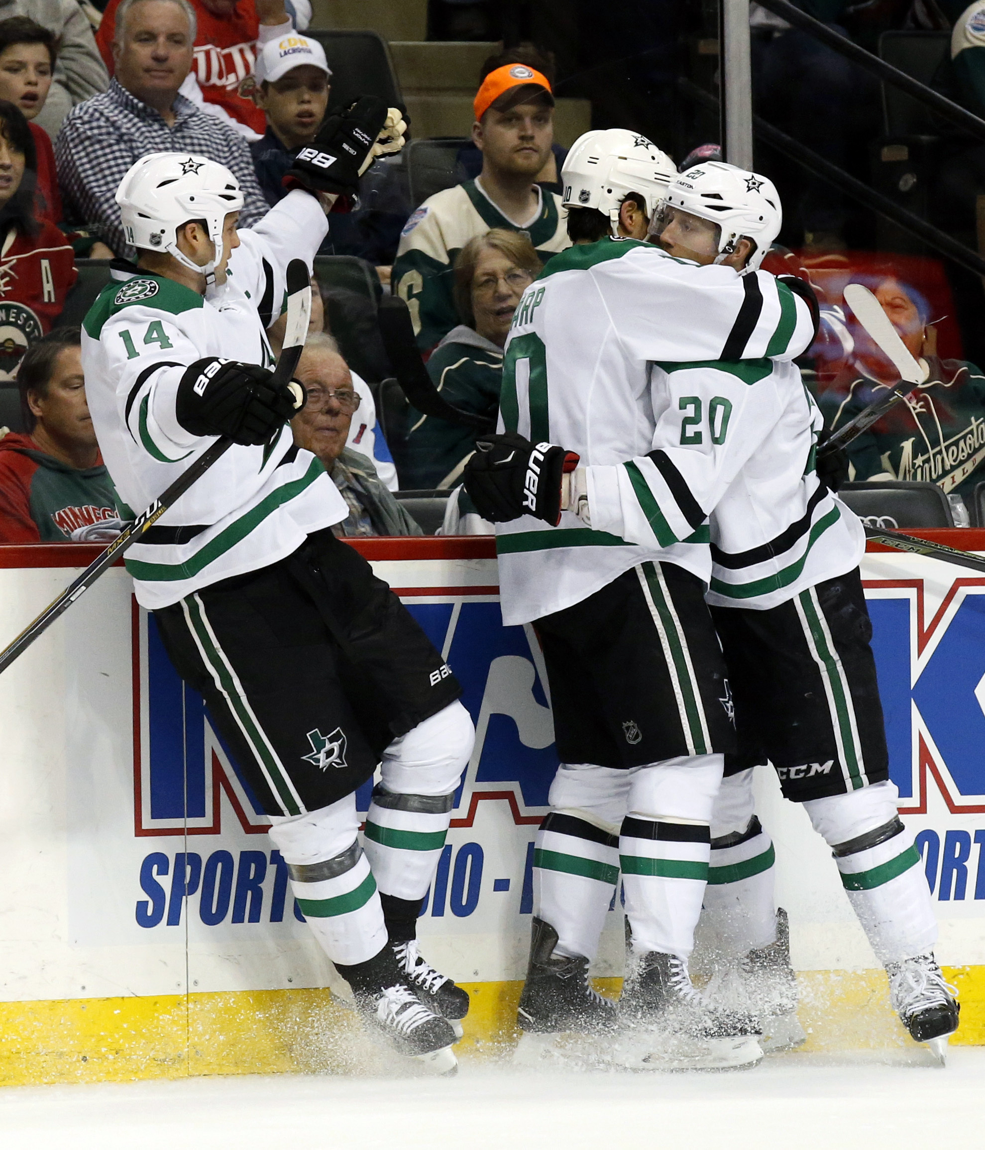 Dallas Stars left wing Patrick Sharp, center, celebrates with teammates  Cody Eakin (20) and Jamie Benn (14) after scoring on Minnesota Wild goalie Devan Dubnyk during the first period of Game 6 in the first round of the NHL Stanley Cup hockey playoffs in