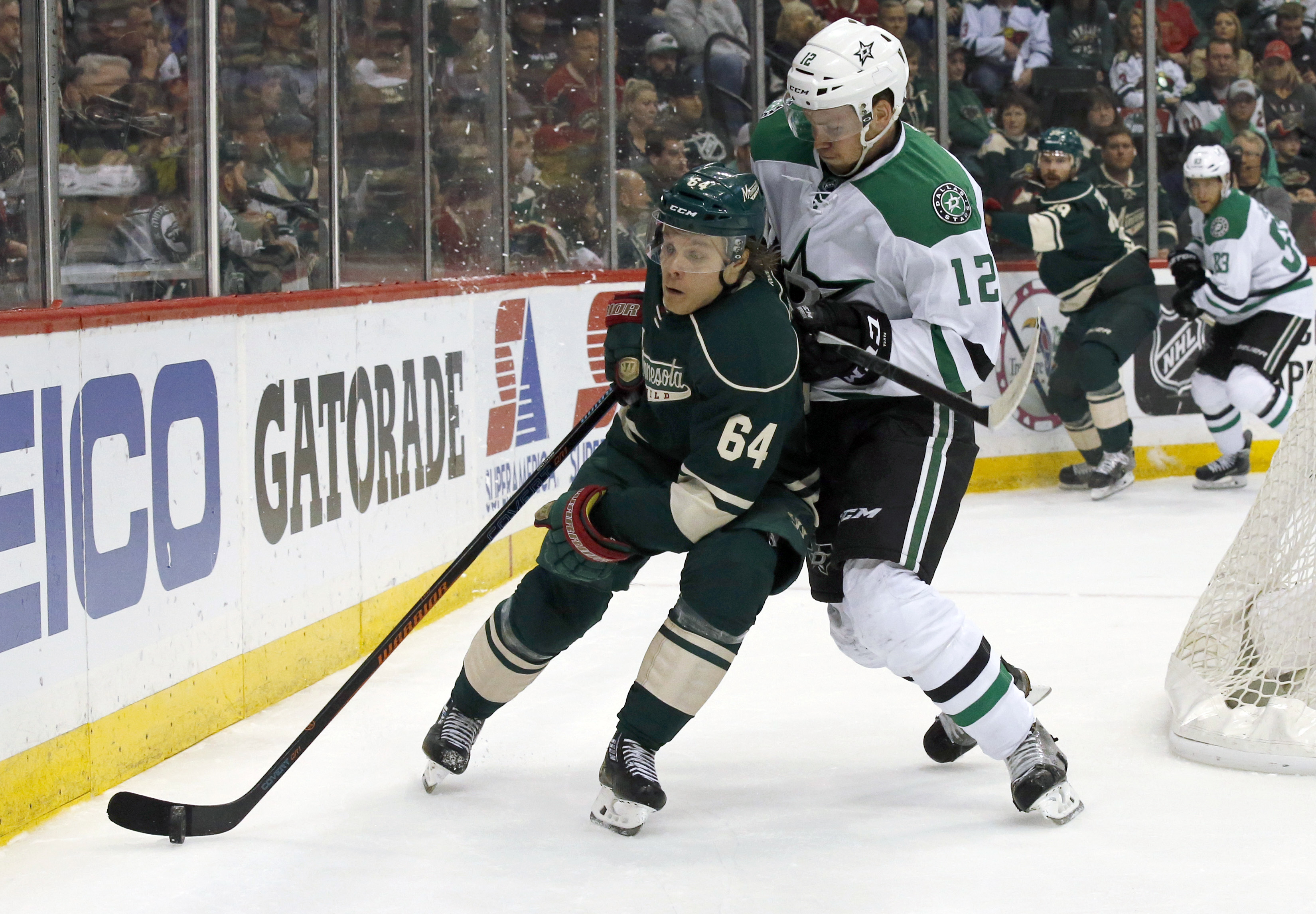 Minnesota Wild center Mikael Granlund (64) and Dallas Stars center Radek Faksa (12) battle for the puck during the first period of Game 6 in the first round of the NHL Stanley Cup hockey playoffs in St. Paul, Minn., Sunday, April 24, 2016. (AP Photo/Ann H