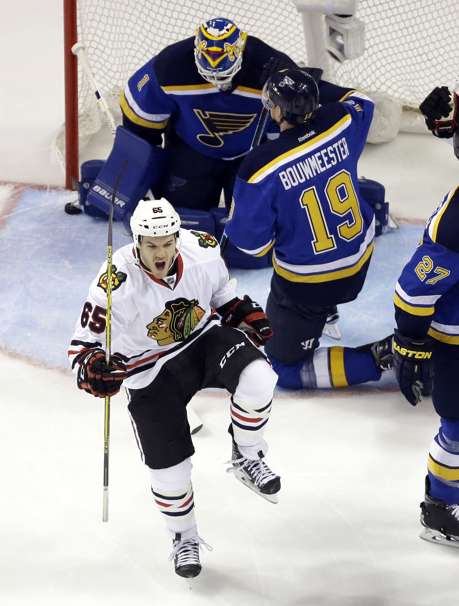 Chicago Blackhawks' Andrew Shaw (65) celebrates after scoring past St. Louis Blues goalie Brian Elliott and Jay Bouwmeester (19) during the second period in Game 7 of an NHL hockey first-round Stanley Cup playoff series Monday, April 25, 2016, in St. Loui