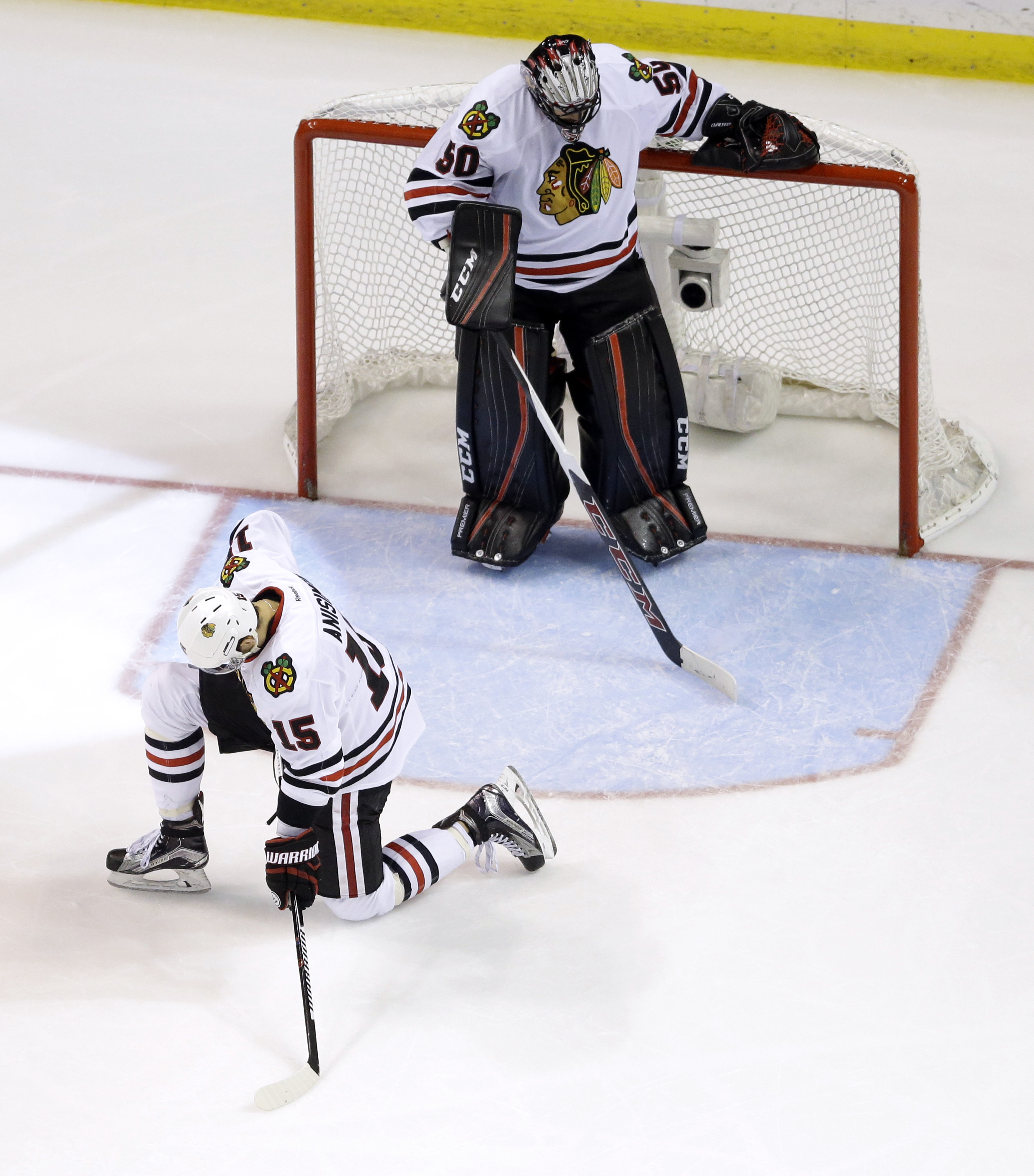 Chicago Blackhawks goalie Corey Crawford, top, and teammate Artem Anisimov, of Russia, pause after allowing a goal by St. Louis Blues' Troy Brouwer during the third period in Game 7 of an NHL hockey first-round Stanley Cup playoff series Monday, April 25,