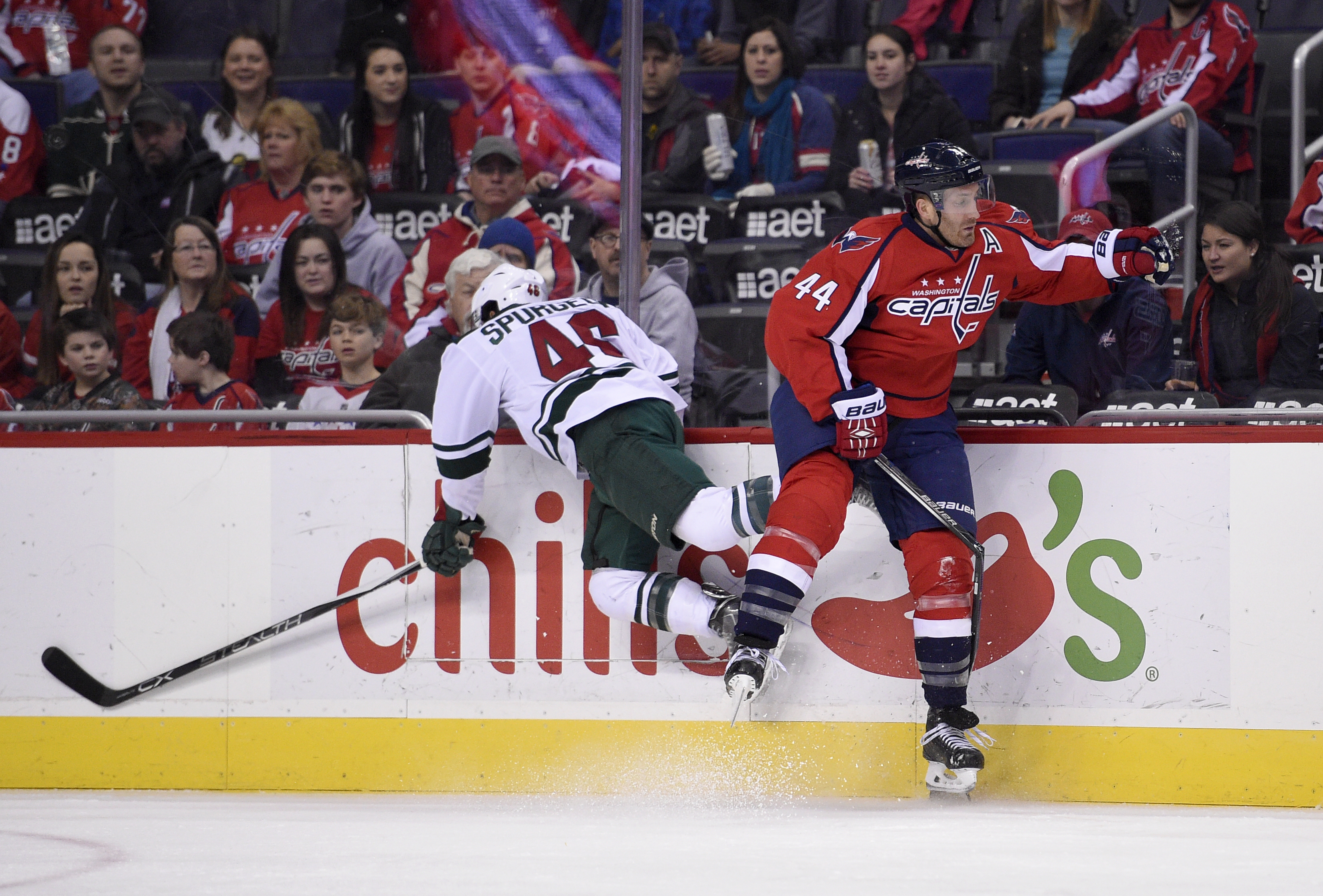 In this photo taken Feb. 26, 2016, Washington Capitals defenseman Brooks Orpik (44) and Minnesota Wild defenseman Jared Spurgeon (46) collide against the boards during the first period of an NHL hockey game in Washington. The Washington Capitals' only maj