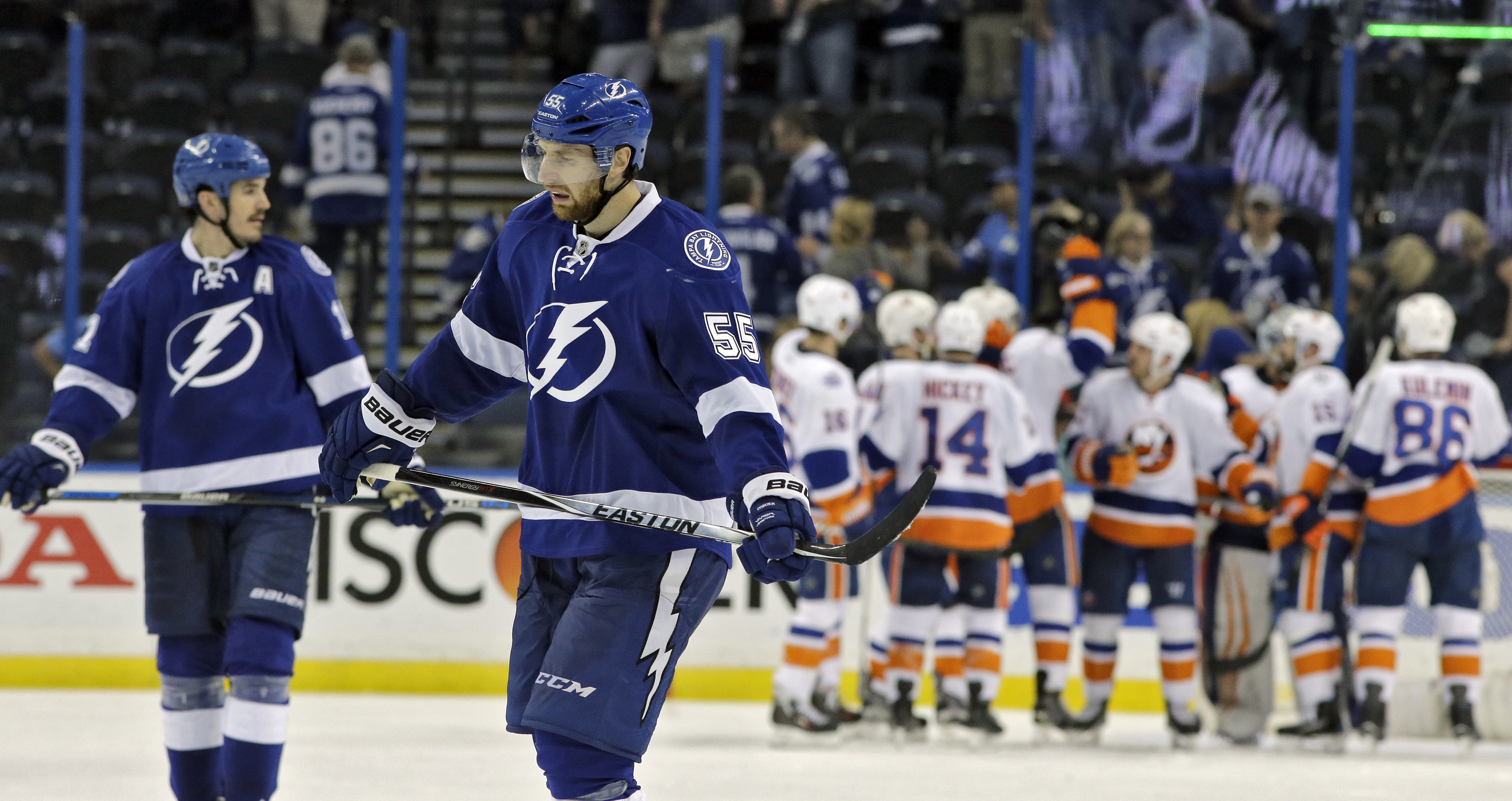 Tampa Bay Lightning center Brian Boyle (11) and defenseman Braydon Coburn (55) skate off as the New York Islanders celebrate a 5-3 win during Game 1 of the NHL hockey Stanley Cup Eastern Conference semifinals Wednesday, April 27, 2016, in Tampa, Fla. (AP