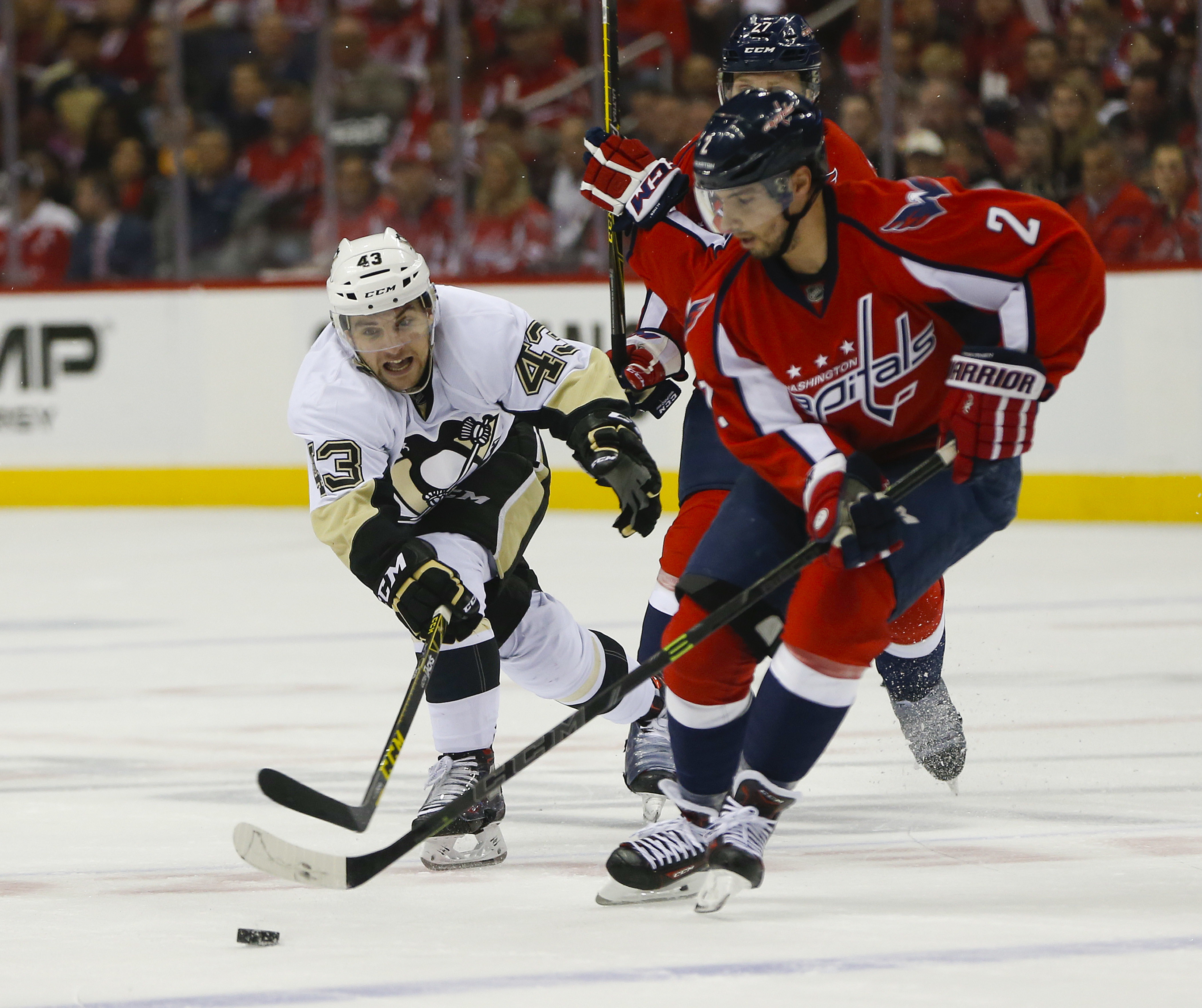 Pittsburgh Penguins left wing Conor Sheary (43) goes up against Washington Capitals defenseman Matt Niskanen (2) and defenseman Karl Alzner (27) for the loose puck during the first period of Game 1 in an NHL hockey Stanley Cup Eastern Conference semifinal