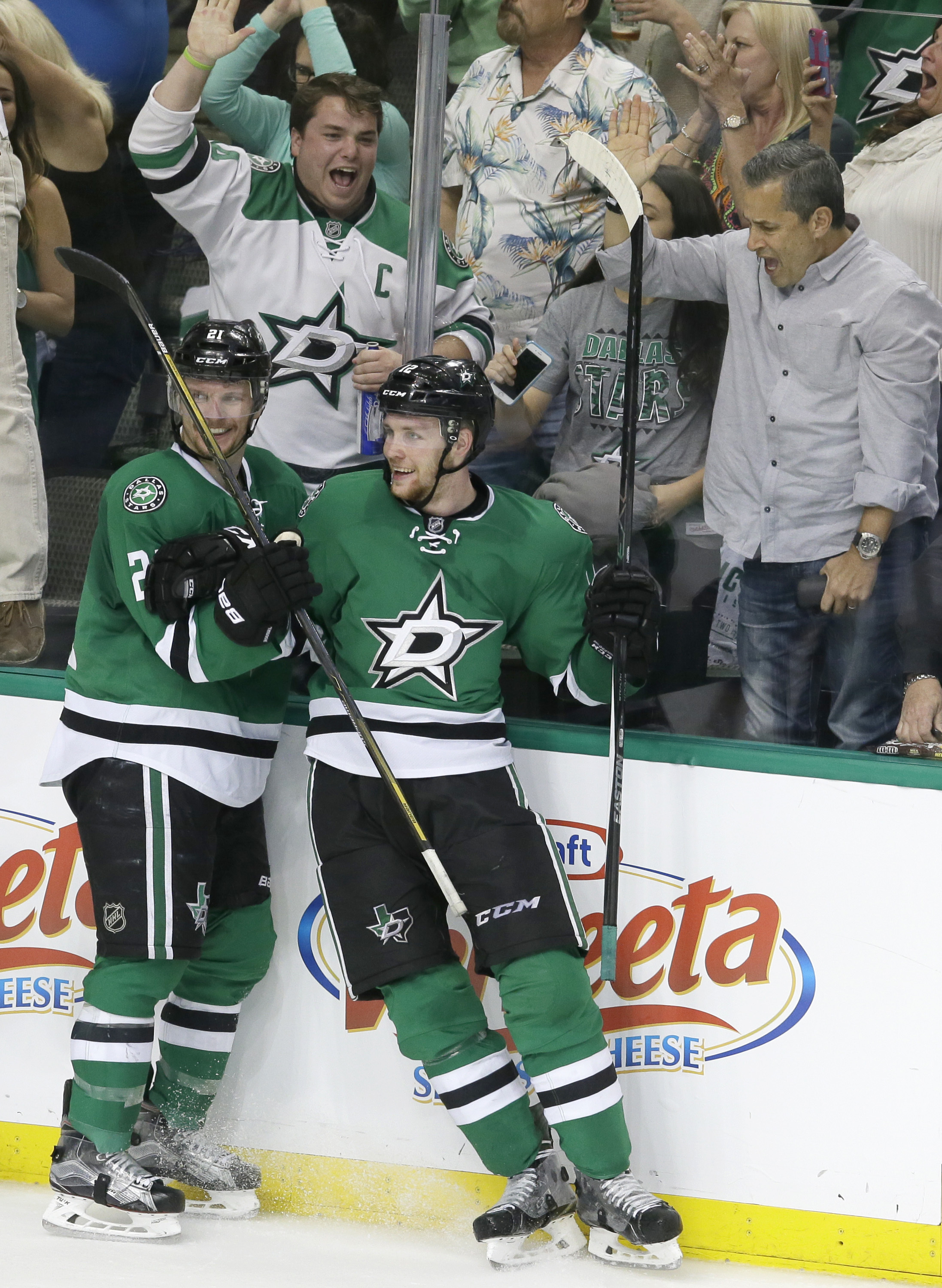 Fans, background, react as Dallas Stars center Radek Faksa (12) celebrates his goal with teammate Antoine Roussel (21) during the third period in Game 1 in the second round of the NHL Stanley Cup playoffs against the St. Louis Blues, Friday, April 29, 201