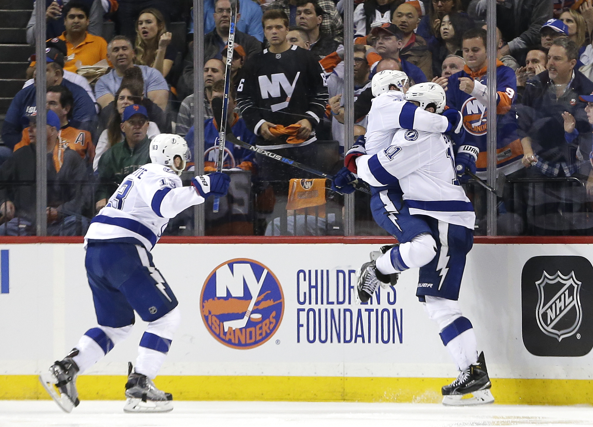 Tampa Bay Lightning right wing Ryan Callahan, center, jumps into the arms of center Brian Boyle (11) as Tampa Bay Lightning center Cedric Paquette (13) rushes in after Boyle scored the game-winning goal against the New York Islanders during the overtime p