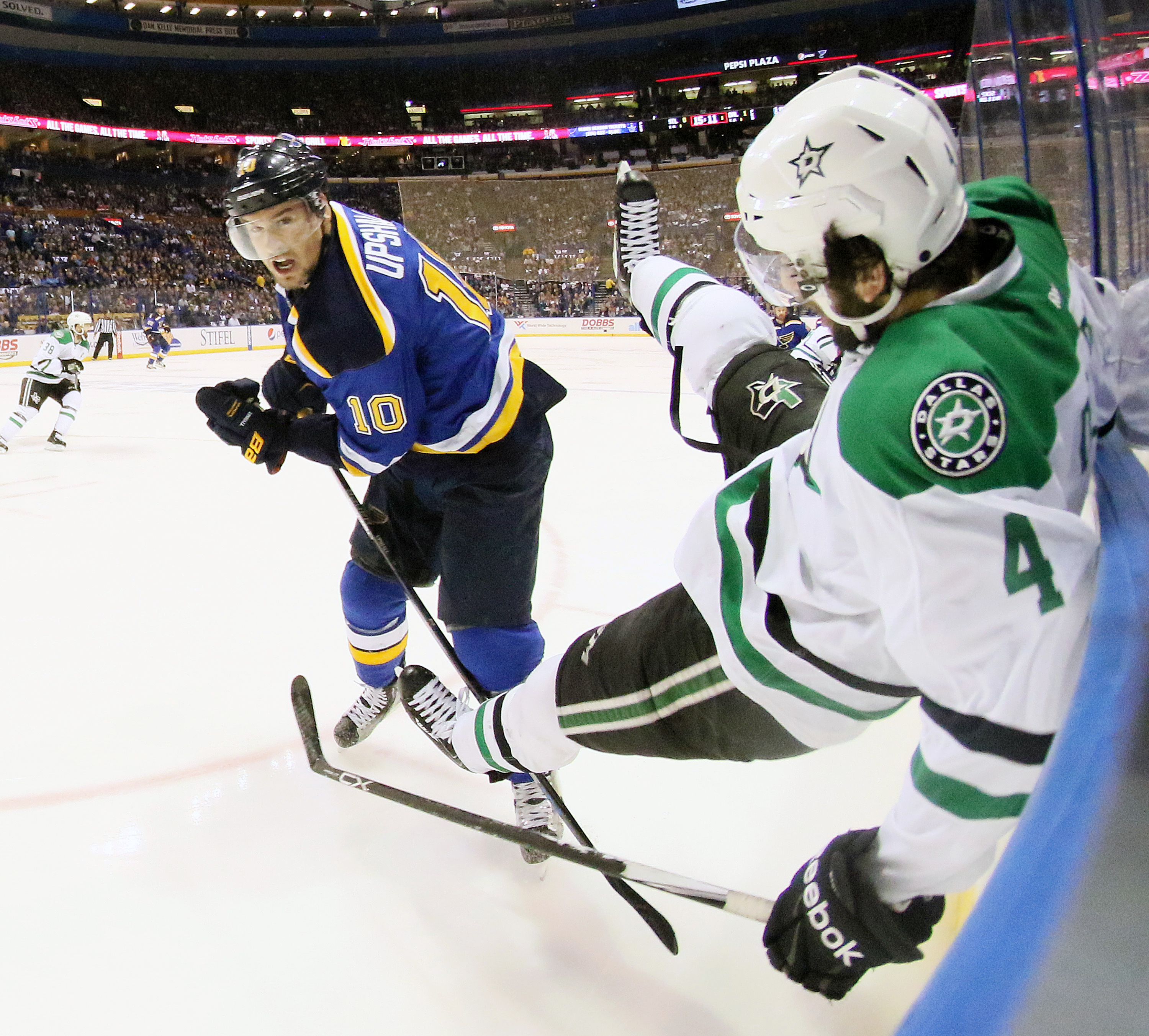St. Louis Blues right wing Scottie Upshall, left, checks Dallas Stars defenseman Jason Demers into the boards in the first period of Game 3 of the NHL hockey Stanley Cup Western Conference semifinals against the Dallas Stars, Tuesday, May 3, 2016, in St.