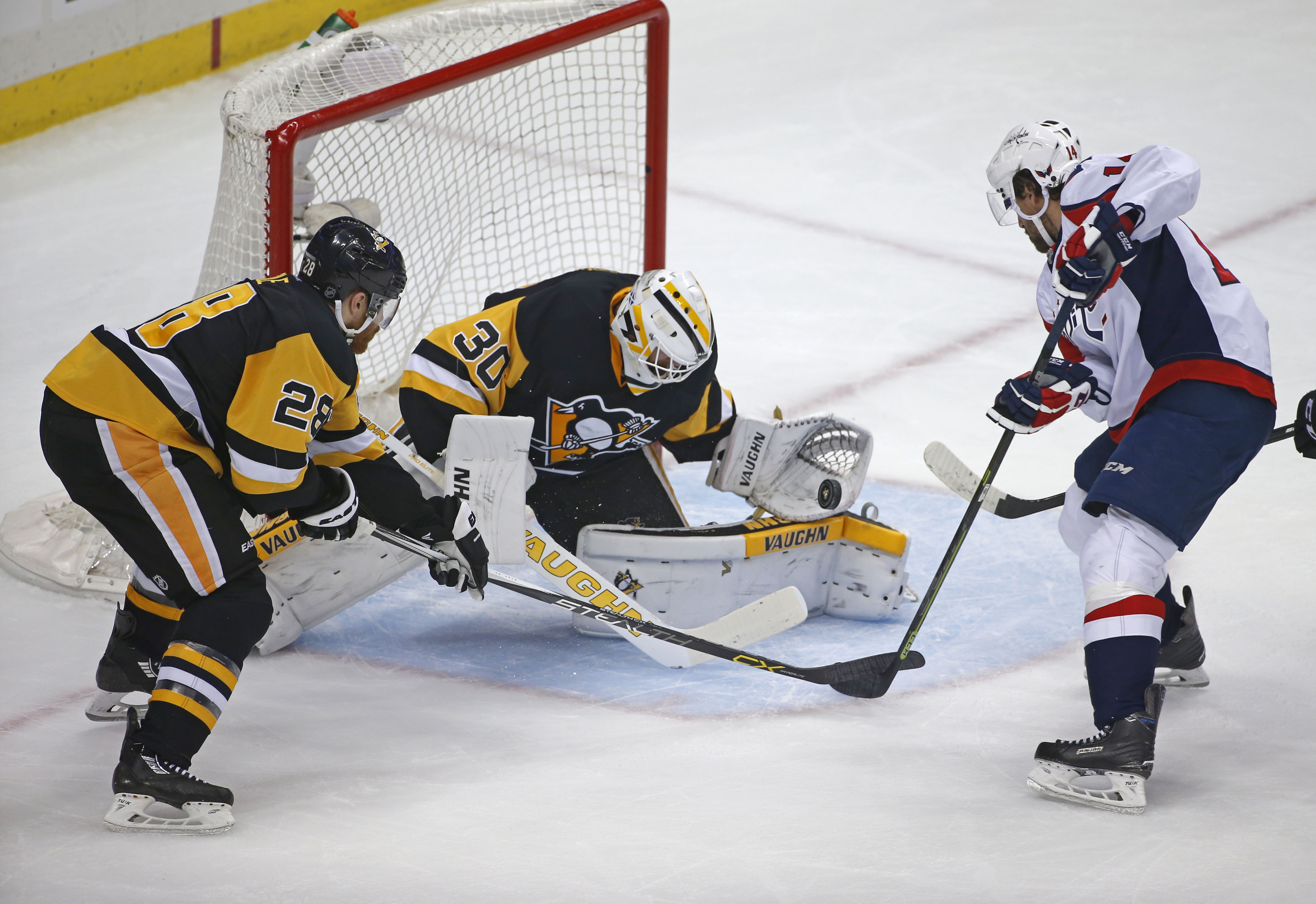 Pittsburgh Penguins goalie Matt Murray (30) makes a save on Washington Capitals Justin Williams (14) as Ian Cole (28) moves in to help during the first period of Game 4 in an NHL hockey Stanley Cup Eastern Conference semifinals in Pittsburgh, Wednesday, M