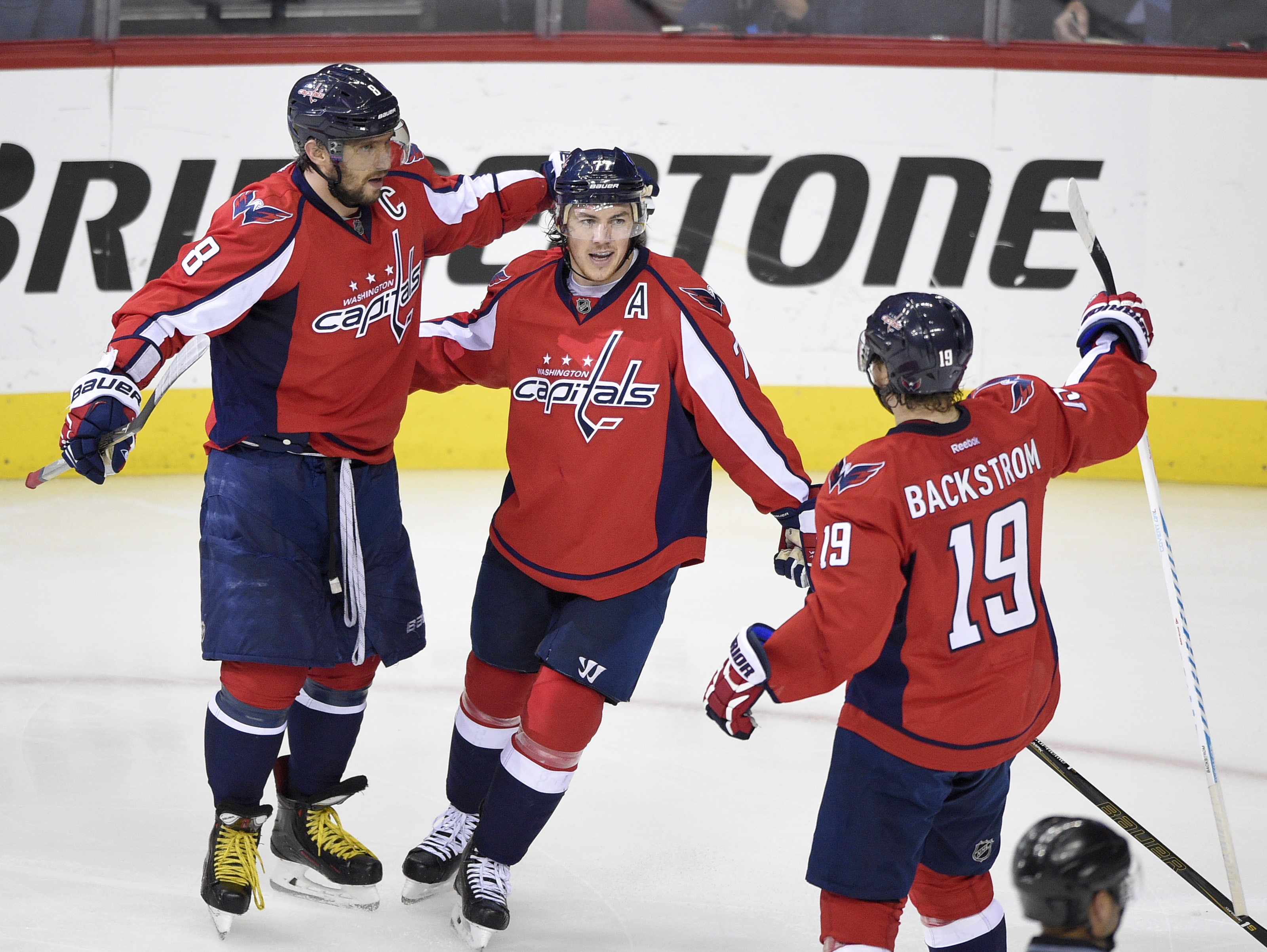 Washington Capitals right wing T.J. Oshie, center, celebrates his goal with Alex Ovechkin (8), of Russia, and Nicklas Backstrom (19), of Sweden, during the second period of Game 5 in an NHL hockey Stanley Cup Eastern Conference semifinals against the Pitt
