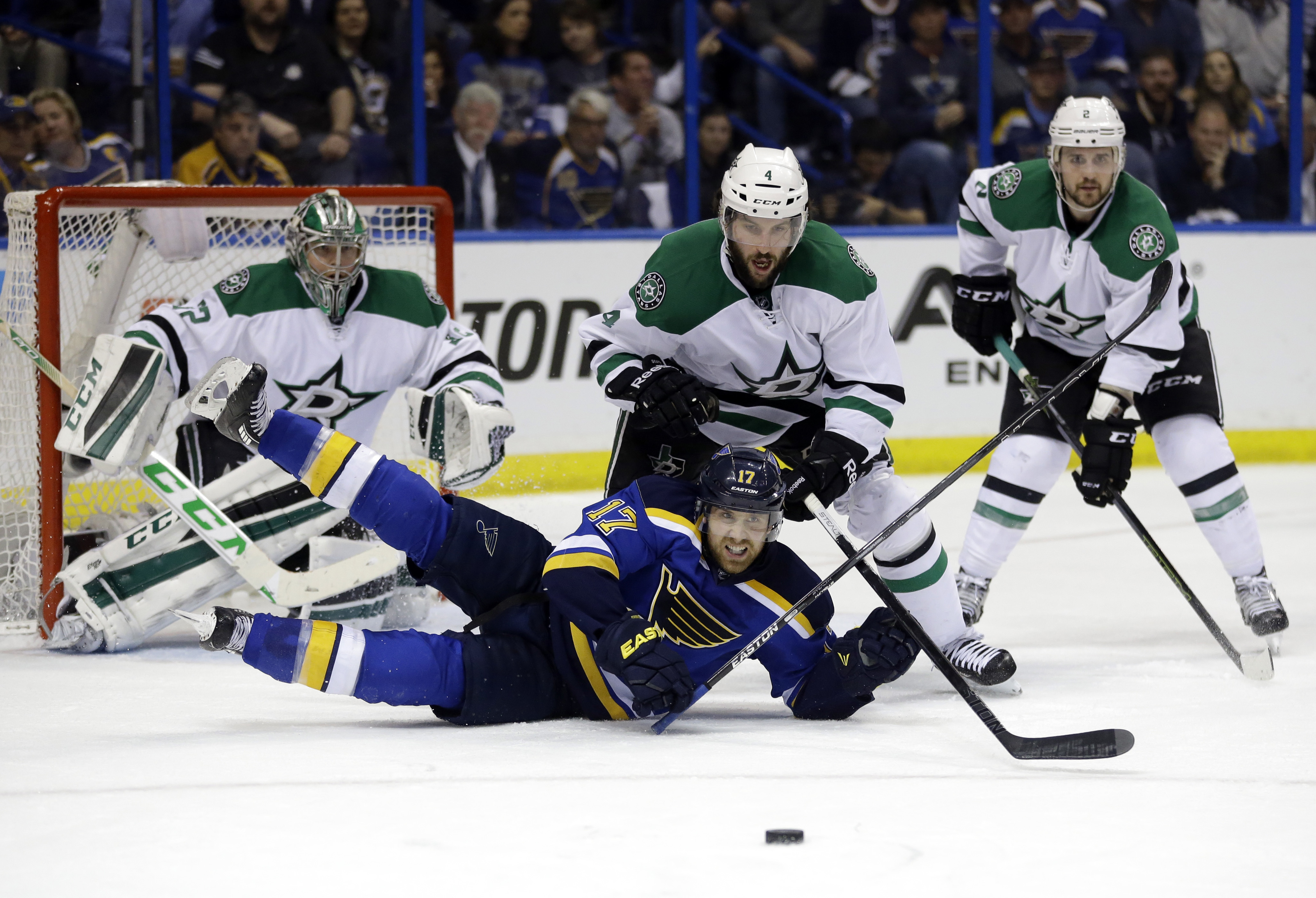 St. Louis Blues' Jaden Schwartz (17) falls while reaching for a puck as Dallas Stars goalie Kari Lehtonen, of Finland, Jason Demers (4) and Kris Russell, right, watch during the second period of Game 6 of the NHL hockey Stanley Cup Western Conference semi