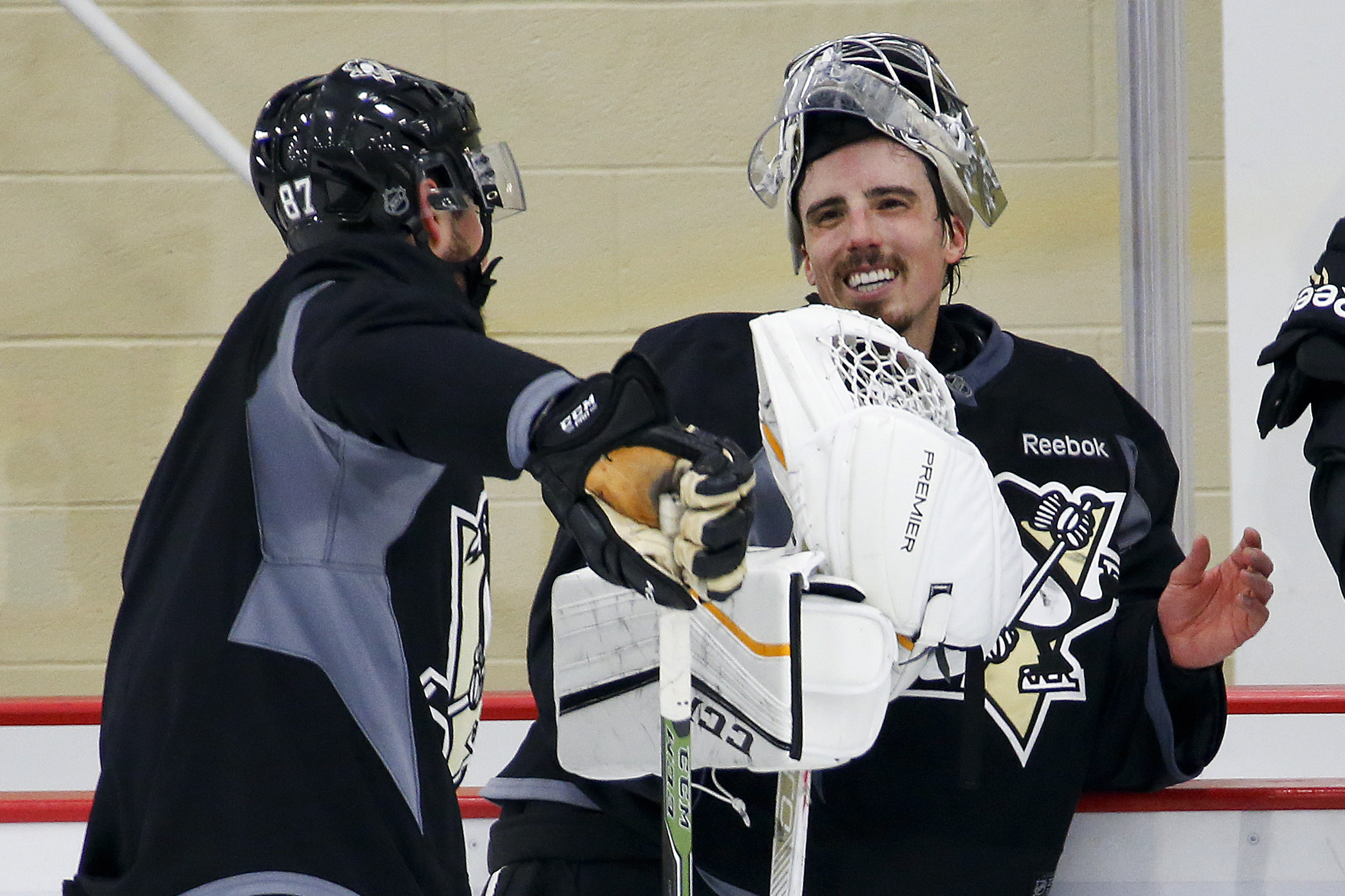 Pittsburgh Penguins goalie Marc-Andre Fleury, right, talks with teammate Sidney Crosby (87) during an NHL hockey practice at UPMC Lemieux Sports Center in Cranberry Township, Pa., Sunday, May 15, 2016. The Penguins were preparing for Game 2 of the Eastern