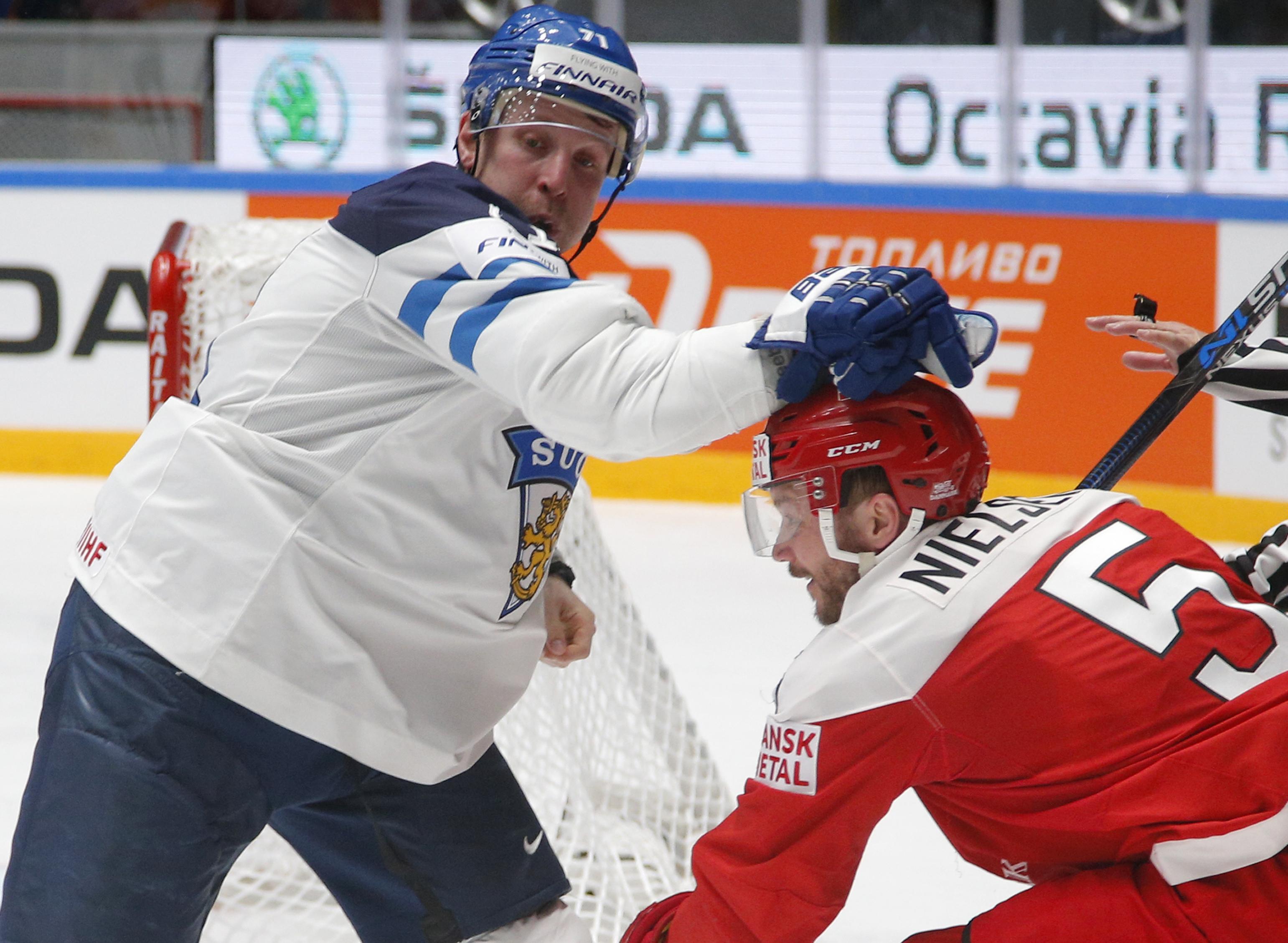 Leo Komarov of Finland, left, challenges Denmarks Daniel Nielsen during the Hockey World Championships quarterfinal match between Finland and Denmark in St.Petersburg, Russia, Thursday, May 19, 2016. (AP Photo/Dmitri Lovetsky)