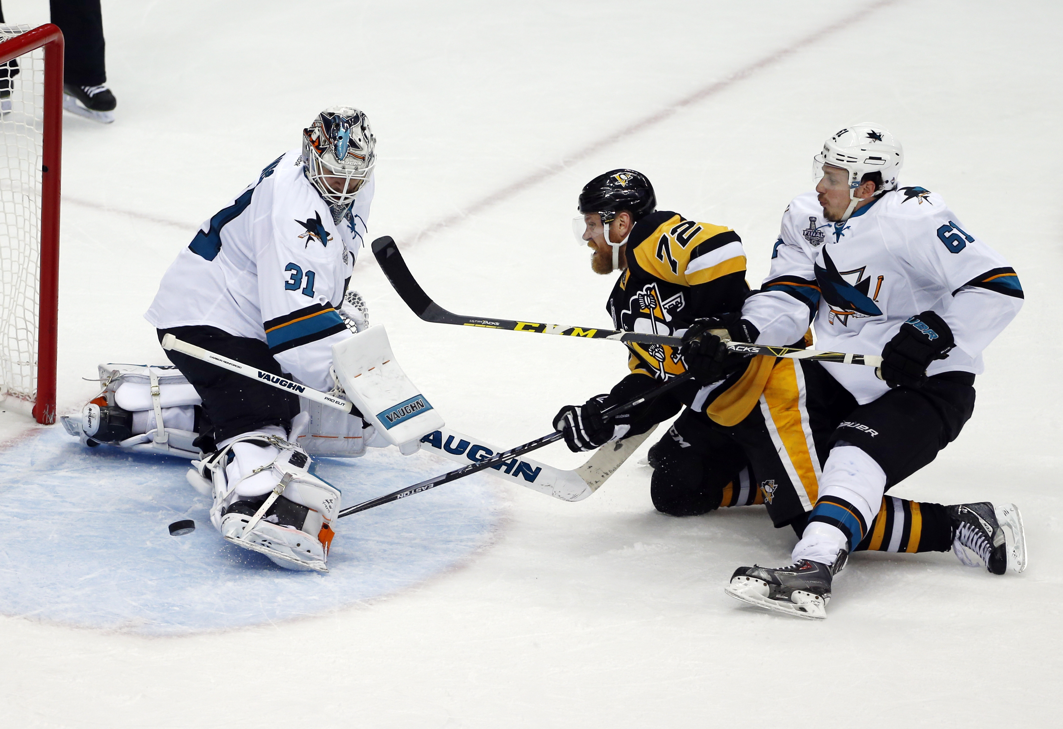 San Jose Sharks goalie Martin Jones (31) turns away a shot by Pittsburgh Penguins' Patric Hornqvist (72) as Sharks' Justin Braun (61) defends during the second period in Game 5 of the NHL hockey Stanley Cup Finals on Thursday, June 9, 2016, in Pittsburgh.