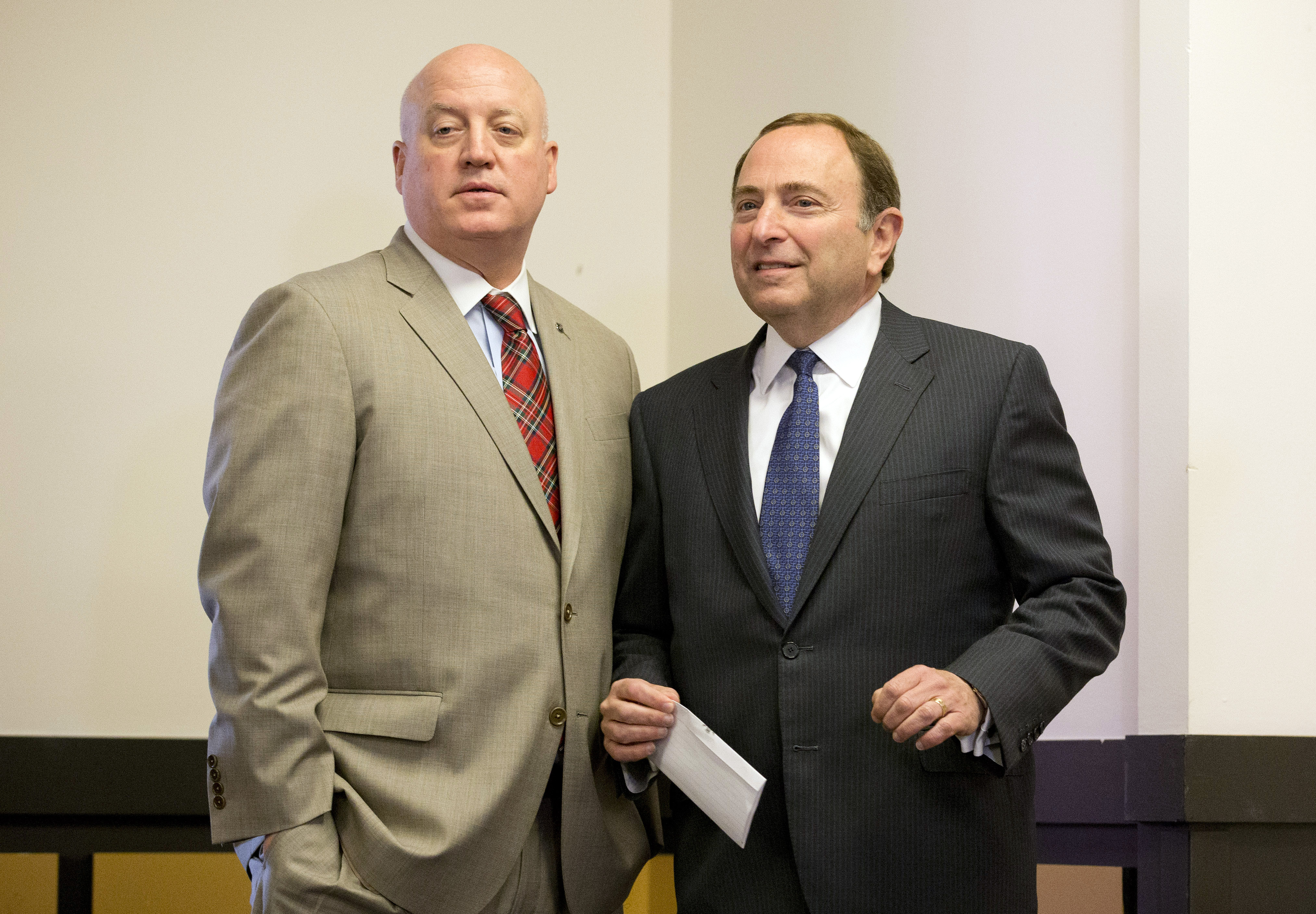 FILE - In this Dec. 9, 2014, file photo, NHL hockey commissioner Gary Bettman, right, and deputy commissioner Bill Daly pause before starting a news conference after attending an NHL owners meeting in Boca Raton, Fla. Bill Foley is trying to bring an NHL