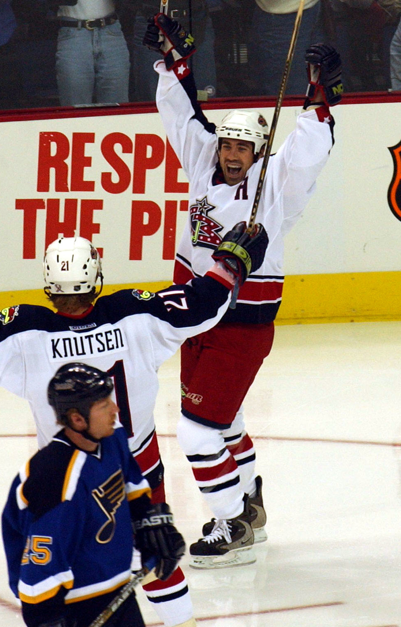 FILE - In this Oct. 4, 2001, file photo, Columbus Blue Jackets' Geoff Sanderson celebrates with teammate Espen Knutsen, center, after scoring a goal against the St. Louis Blues in an NHL hockey game in Columbus, Ohio. Blues' Mike Keane skates by at lower