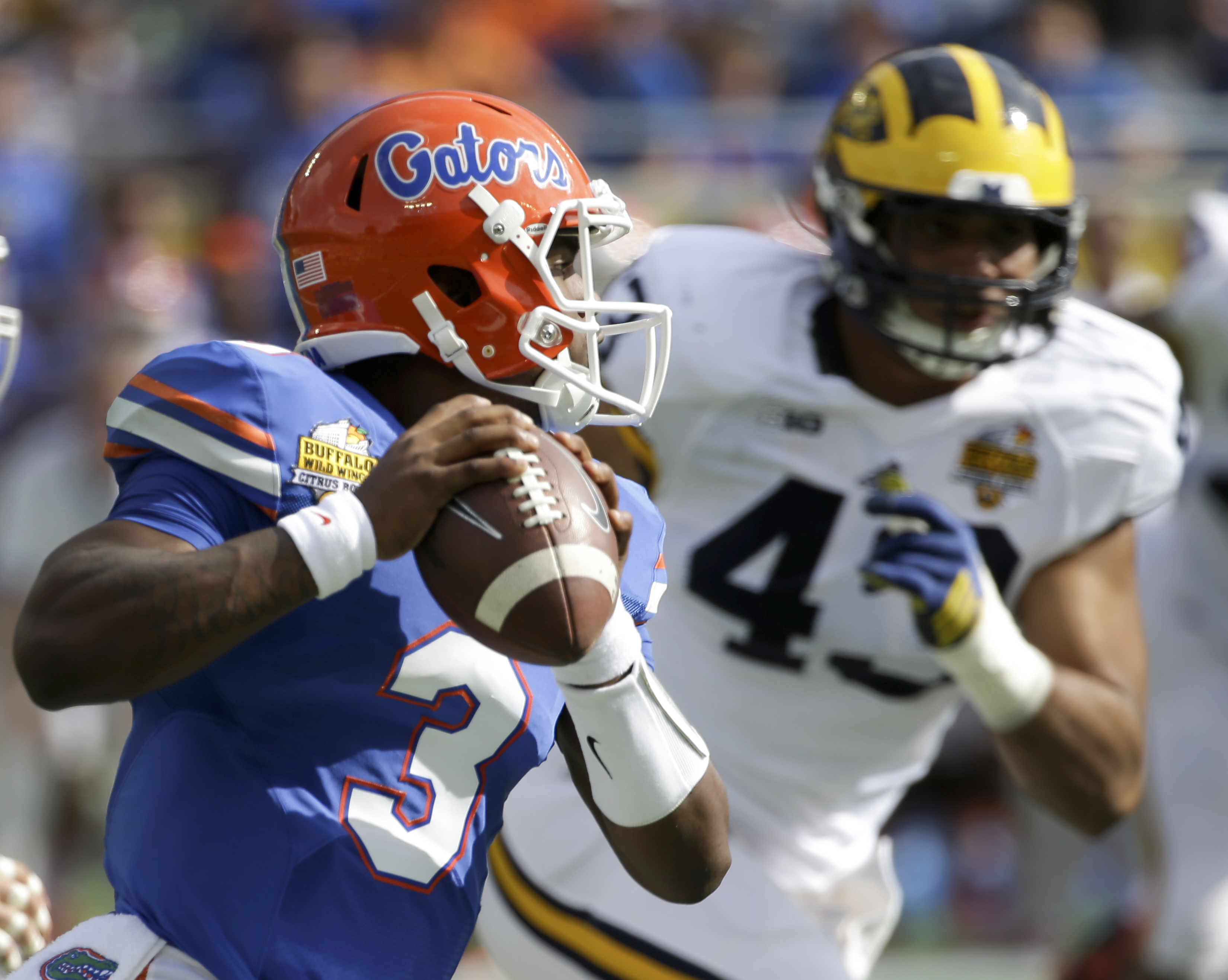 Florida quarterback Treon Harris (3) looks for a receiver as he is pressured by Michigan defensive end Chris Wormley (43) during the first half of the Citrus Bowl NCAA college football game, Friday, Jan. 1, 2016, in Orlando, Fla. (AP Photo/John Raoux)