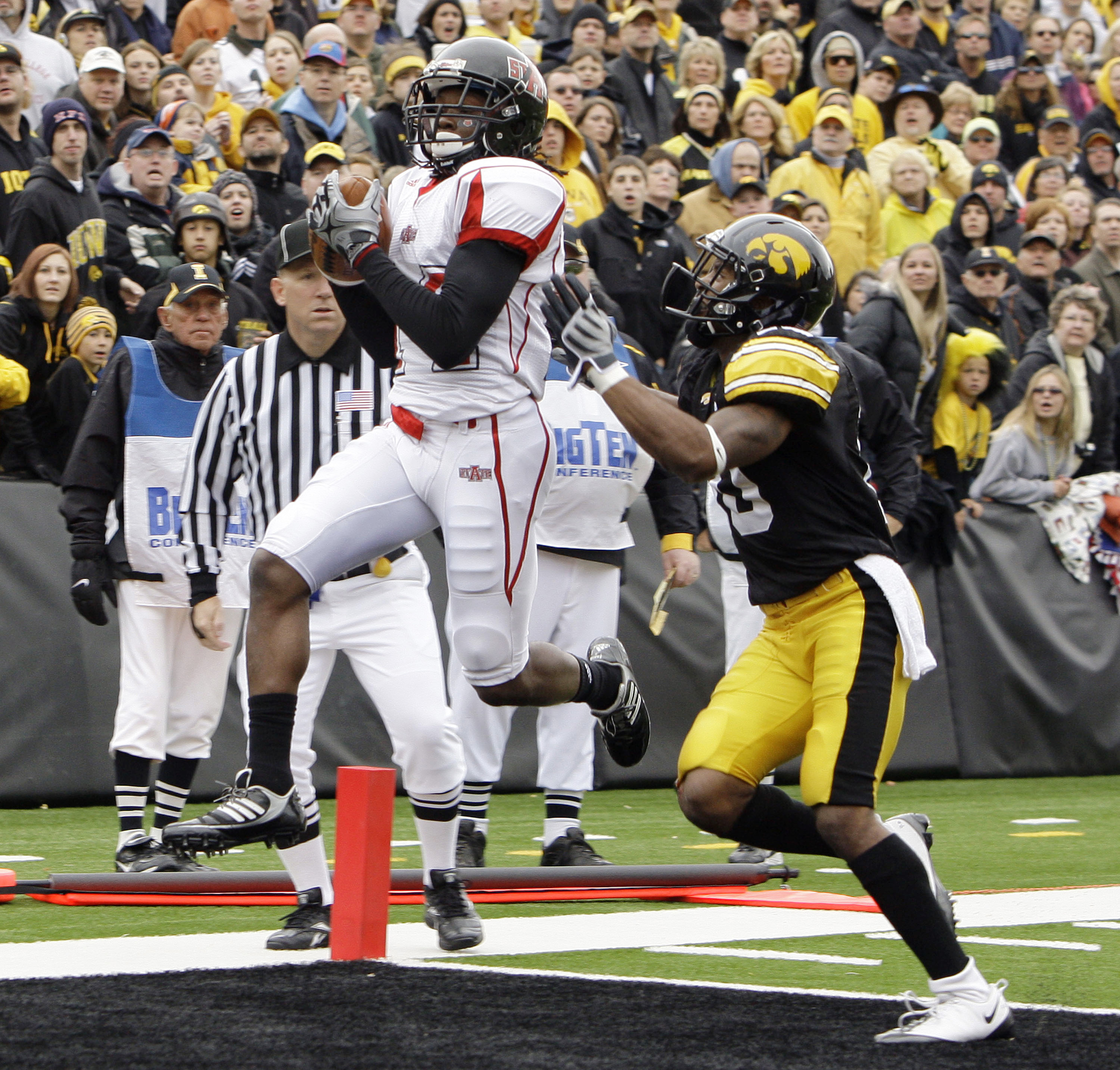 FILE -  In this Oct. 3, 2009, file photo, Arkansas State's Brandon Thompkins, left, catches a touchdown pass over Iowa's William Lowe during the second quarter of an NCAA college football game in Iowa City, Iowa. The University of Iowa settled a lawsuit F