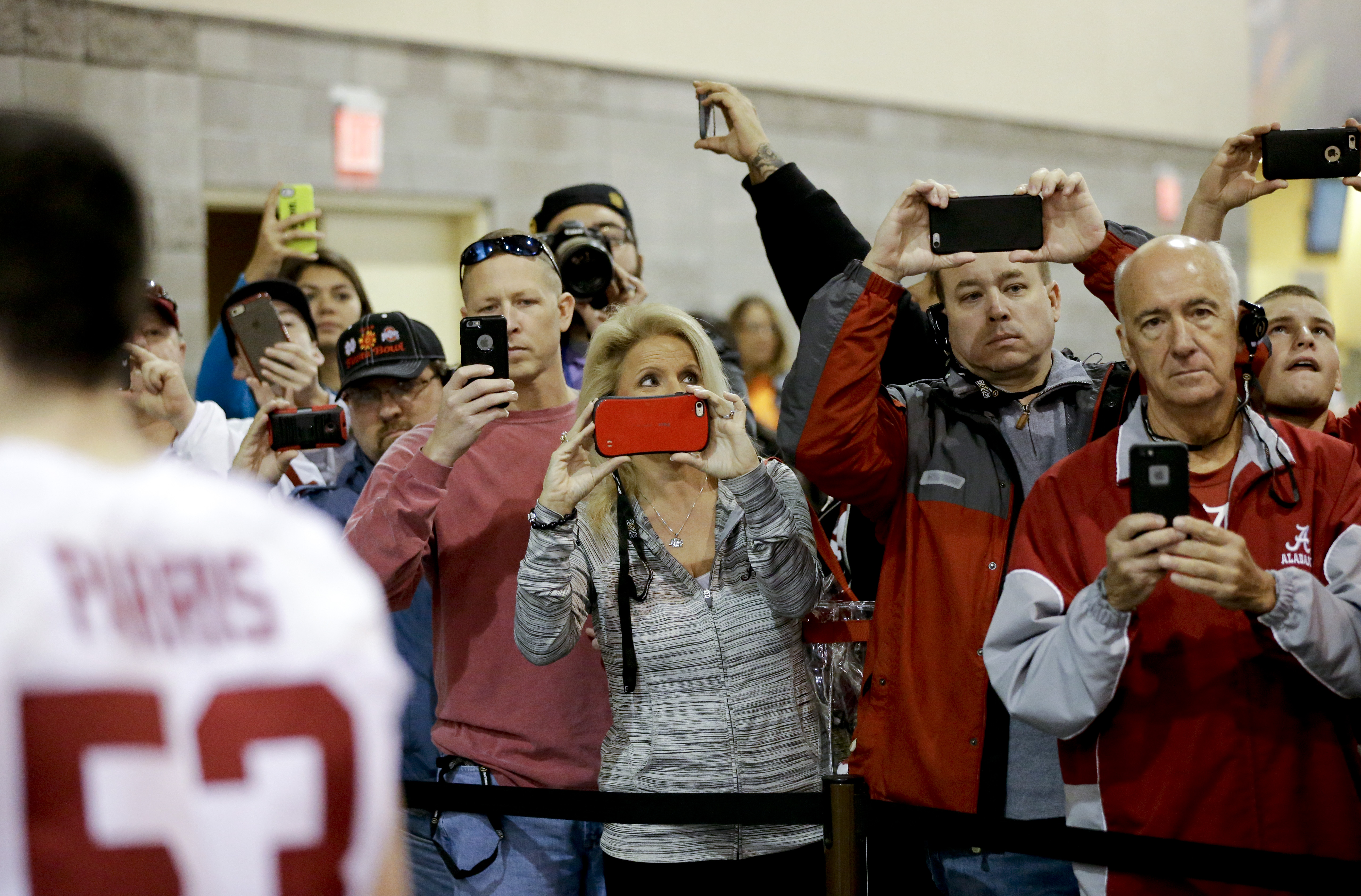 Fans take pictures as the team from Alabama leaves after media day for the NCAA College Football Playoff National Championship in Phoenix, Saturday, Jan. 9, 2016. Alabama will face Clemson in Monday's game. (AP Photo/David J. Phillip)