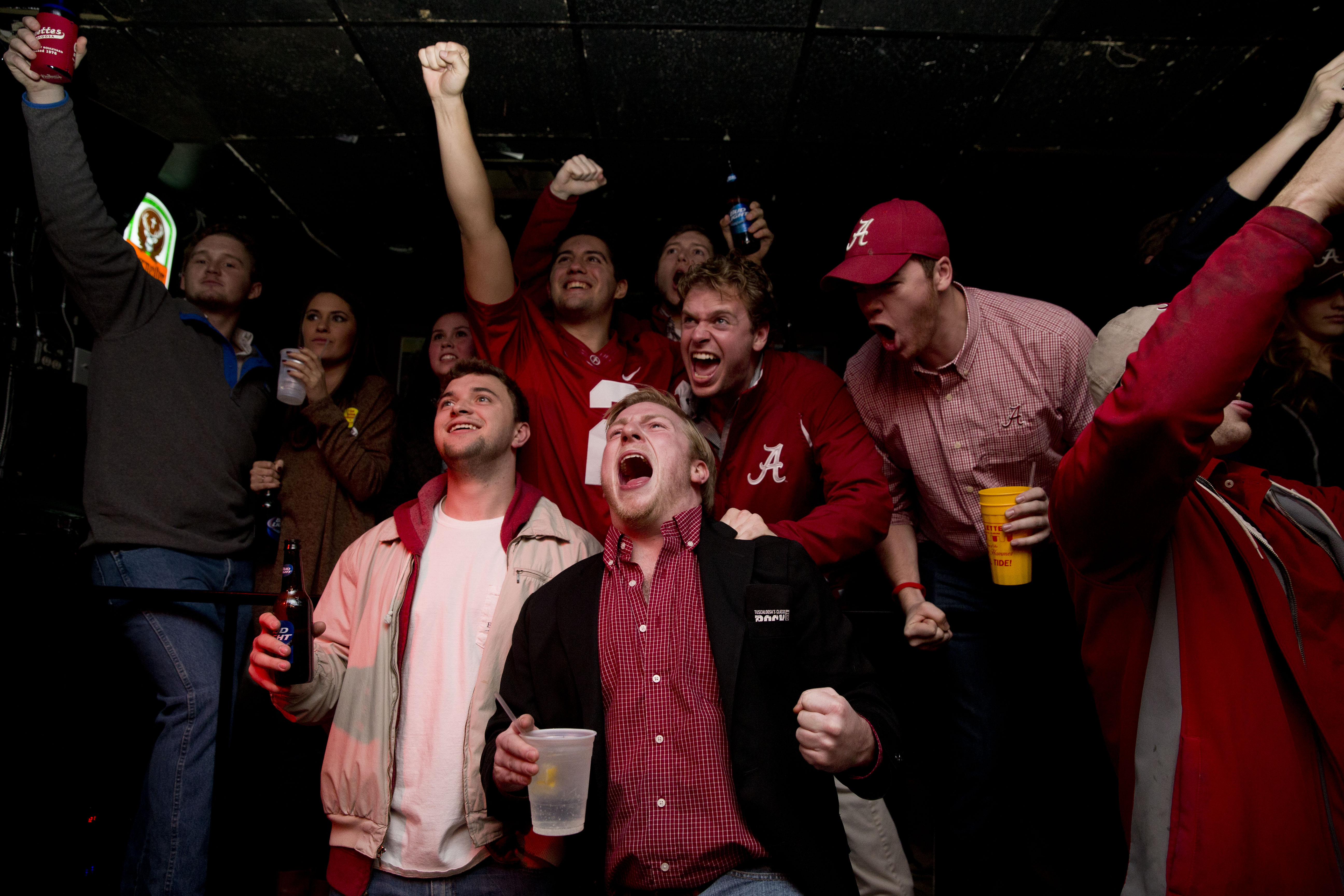 Alabama fans, Joe Kazoiw, center, 22, of Atlanta, Bruce Gurnowski, left, 21, of Newark, N.J., Zach Soto, back left, 21, of Hoover, Ala., and Mark Smith, back right, 22, of Indianapolis, Ind., cheer after a touchdown during the NCAA college playoff champio