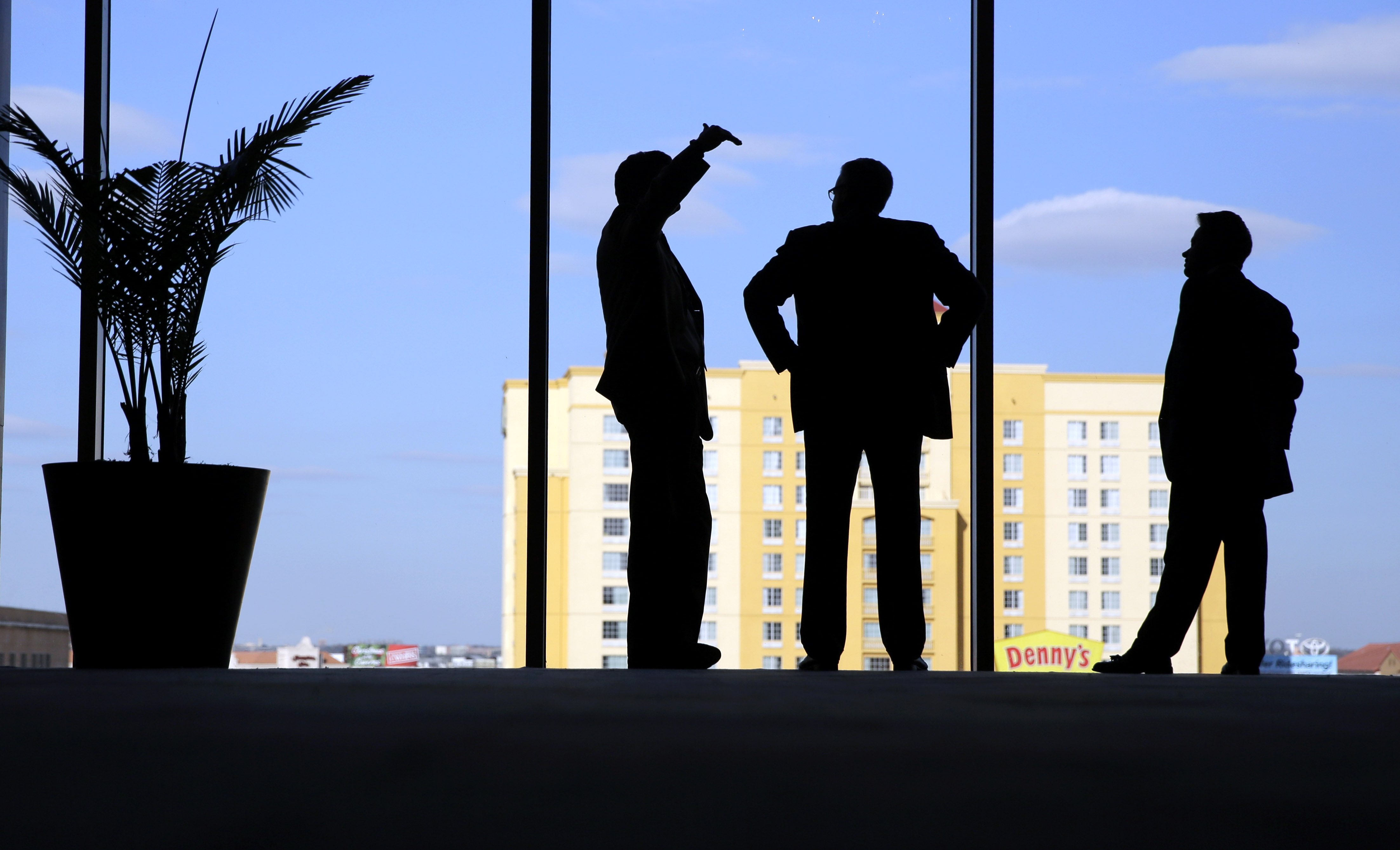 Counsel members talks as they stand at a window during a break in a closed-door meeting at  the NCAA Convention where the Big 12 is pushing to deregulate conference championship games, Wednesday, Jan. 13, 2016, in San Antonio. A move could allow the 10-te