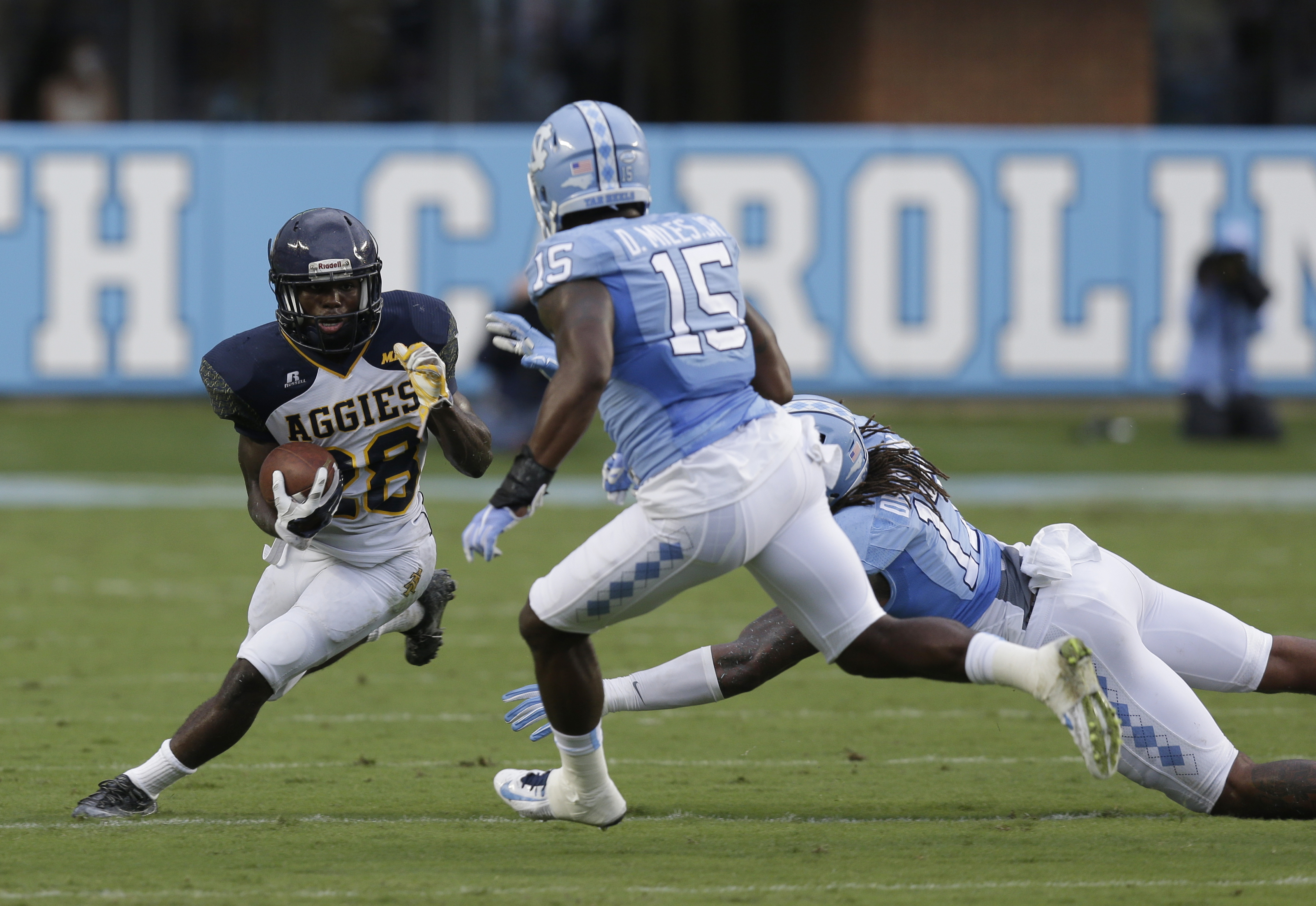 North Carolina's Dajaun Drennon (17) and Donnie Miles (15) move in to tackle North Carolina A&T's Tarik Cohen (28) during the first half of an NCAA college football game in Chapel Hill, N.C., Saturday, Sept. 12, 2015. (AP Photo/Gerry Broome)