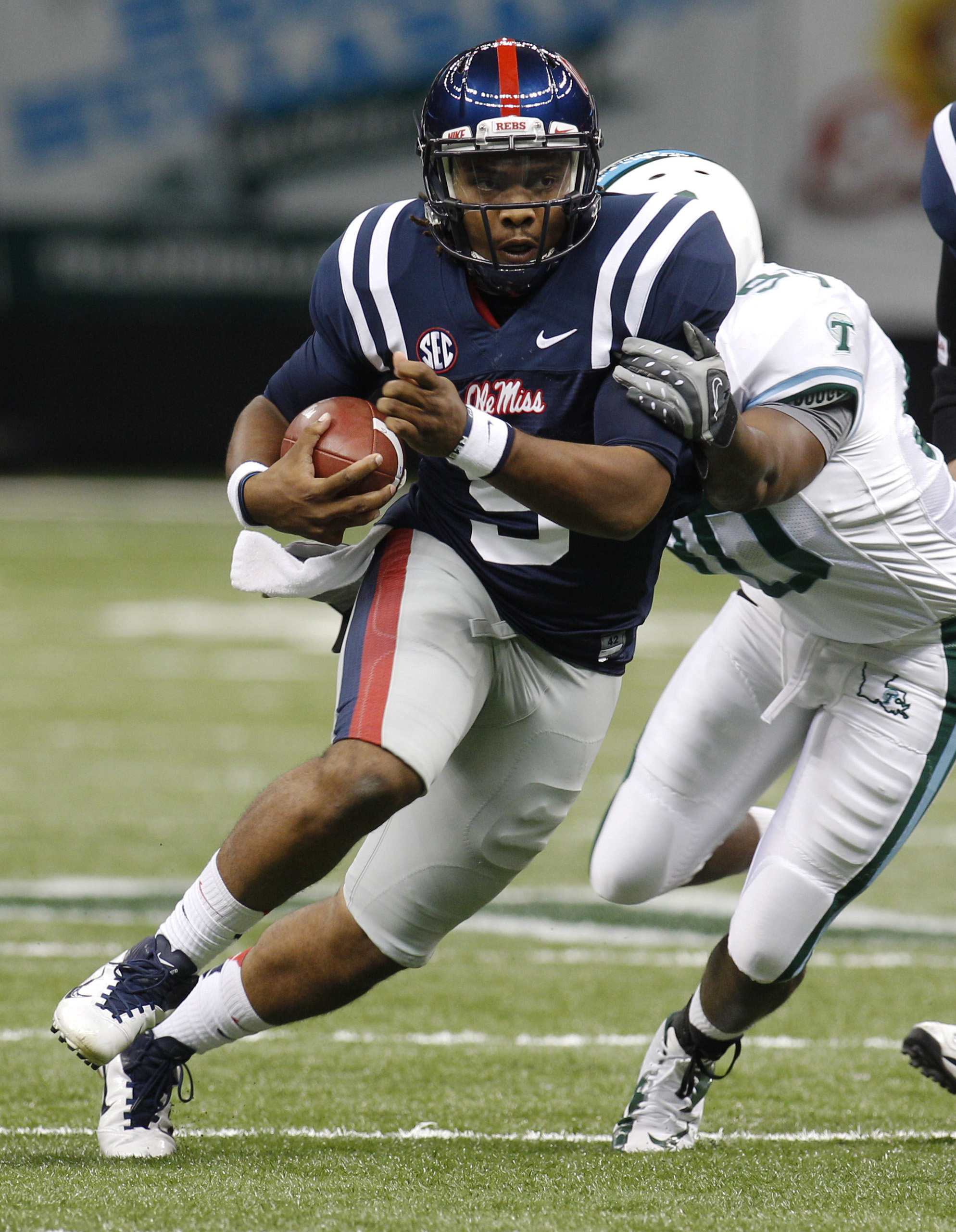 Mississippi quarterback Maikhail Miller (9) scrambles away from Tulane defensive end Wendell Beckwith (90) in the second half of an NCAA college football game in New Orleans,  Saturday, Sept. 22, 2012. (AP Photo/Bill Haber)