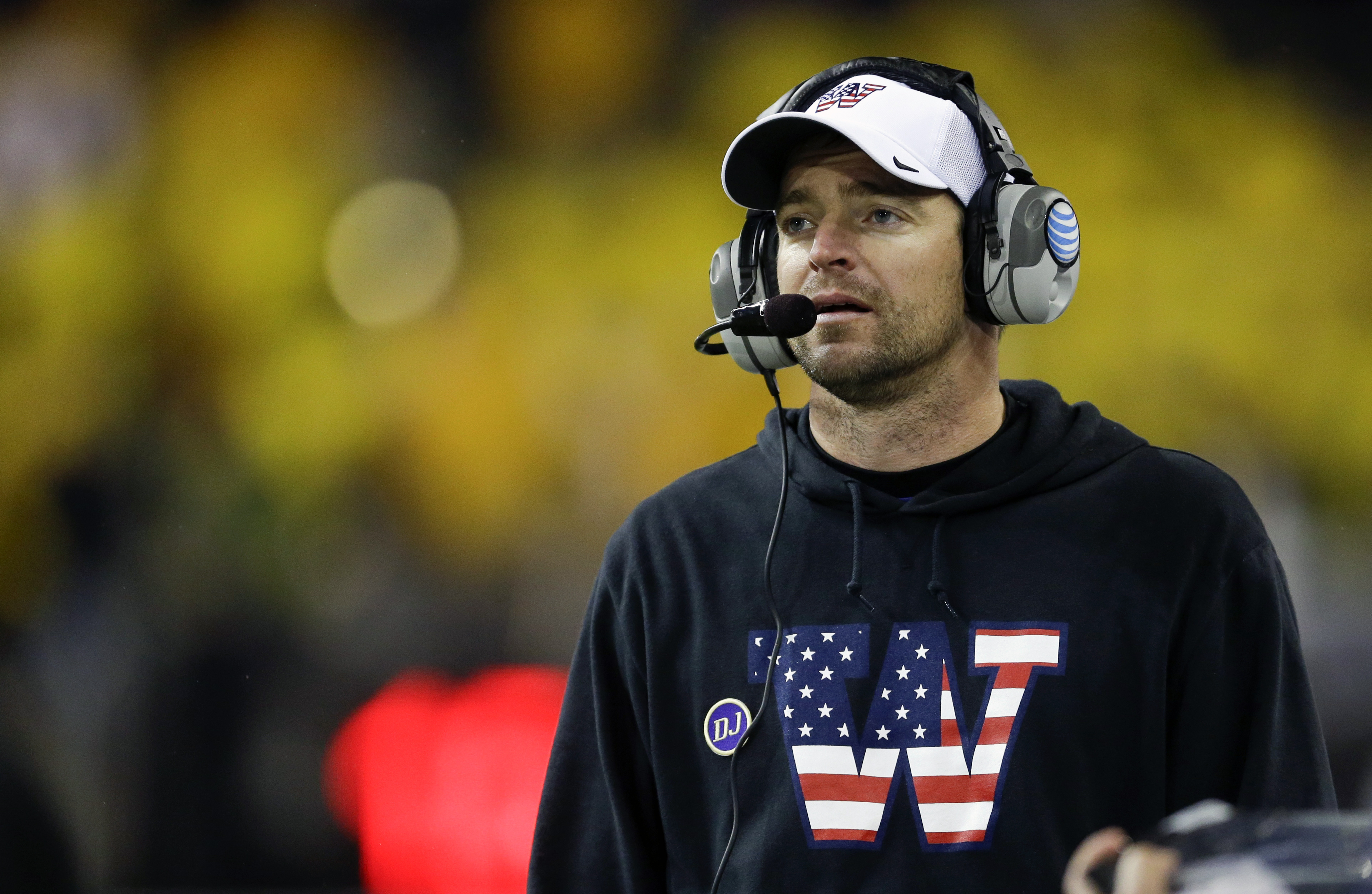 FILE - In this Nov. 9, 2013, file photo, Washington's defensive coordinator Justin Wilcox wears a sweatshirt and cap with a special team logo to honor veterans as he coaches against Colorado in the second half of an NCAA college football game in Seattle.