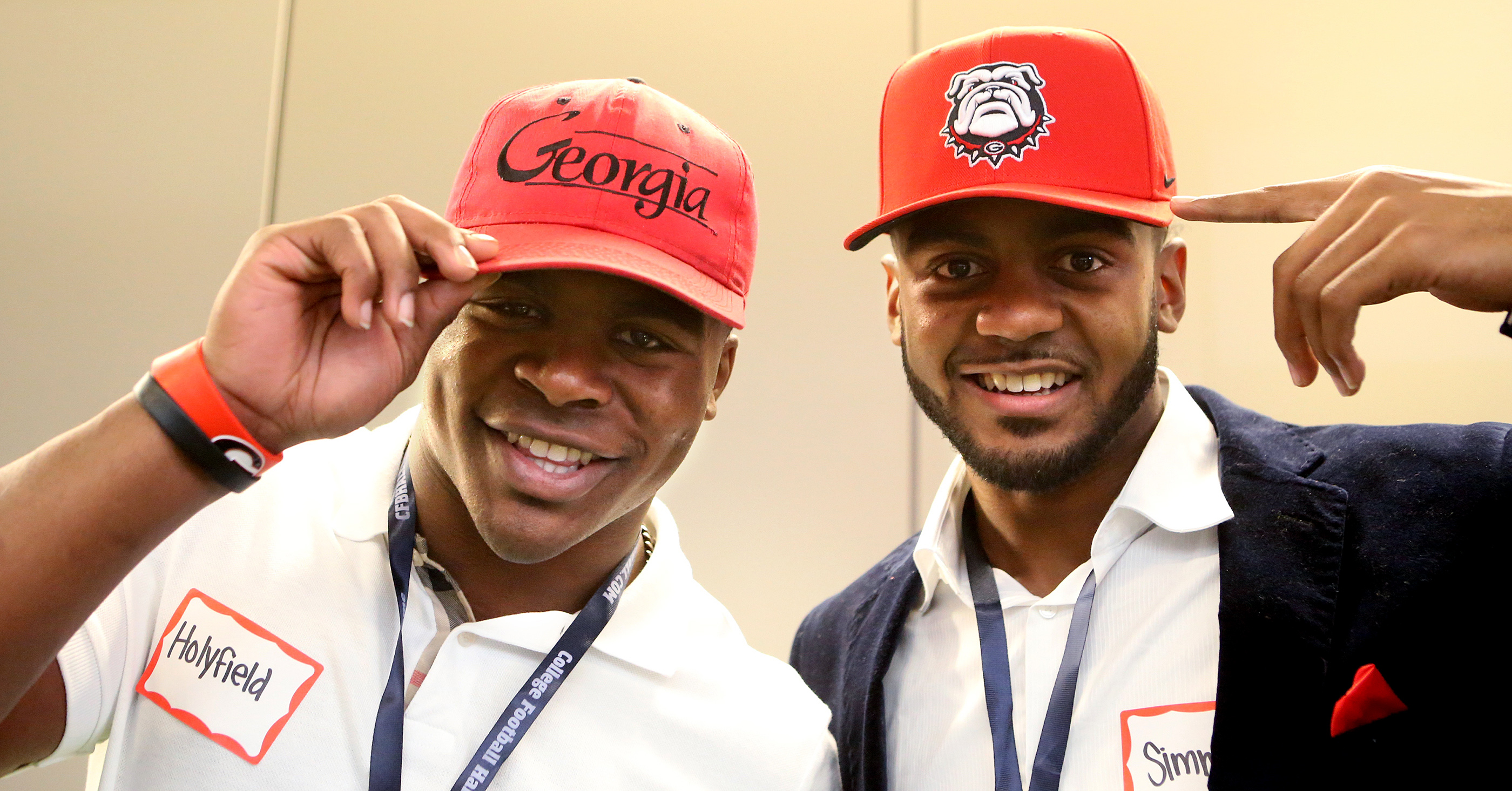 Woodward High School running back Elijah Holyfield, left, and McEachern High School wide receiver Tyler Simmons, don University of Georgia caps during national signing day at the College Football Hall of Fame, Wednesday, Feb. 3, 2016, in Atlanta. (Curtis
