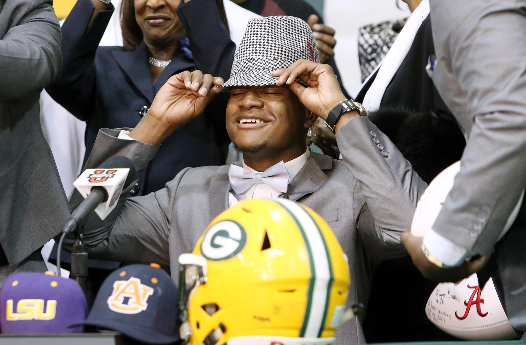 Gordo High School football player Ben Davis, seated beside his parents, Faye and Wayne, dons a houndstooth hat after committing to attend Alabama during a national signing day Program at Gordo High School, Wednesday, Feb. 3, 2016, in Tuscaloosa Ala. (Mich