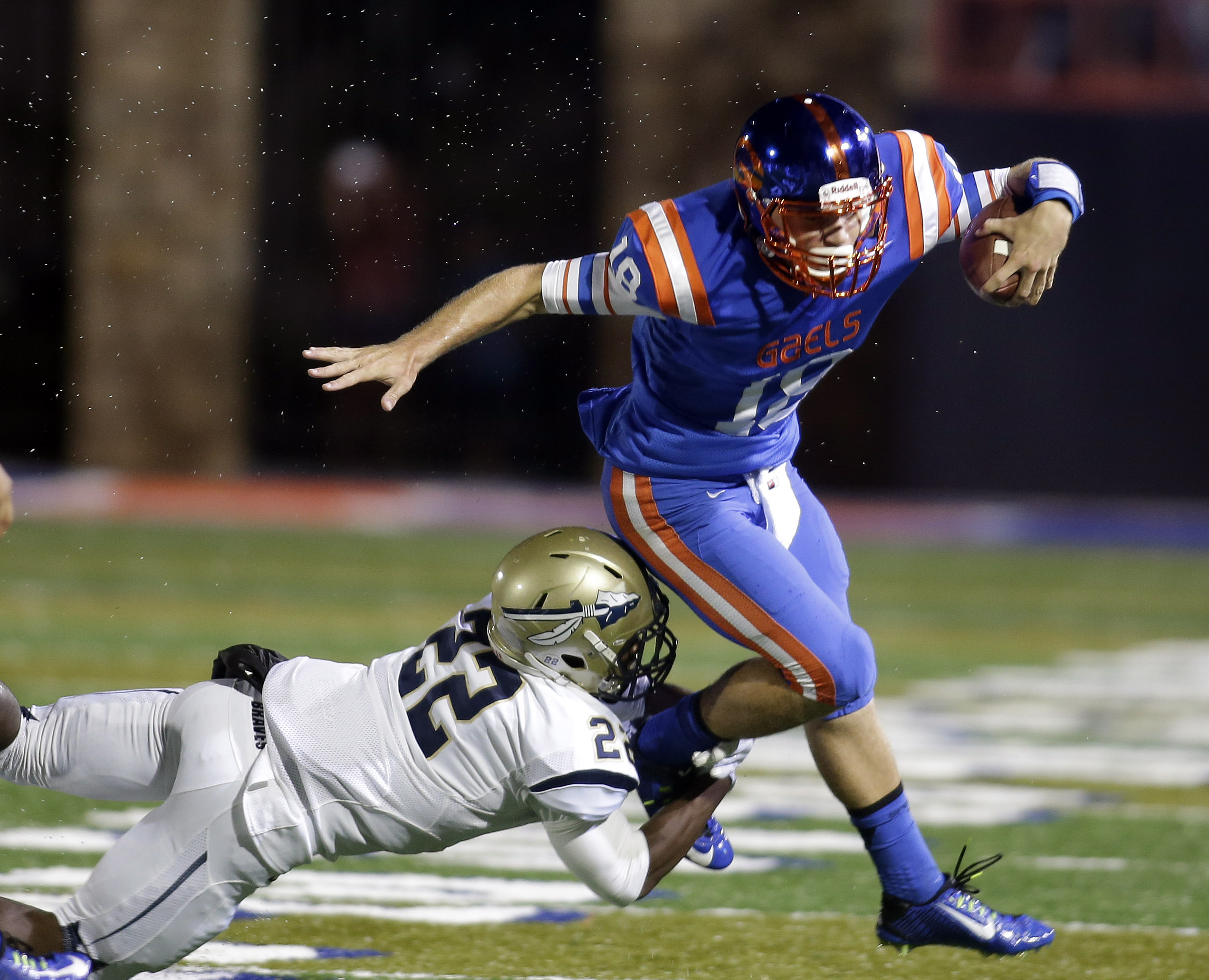FILE - In this Sept. 26, 2014, file photo, Bishop Gorman quarterback Tate Martell is tackled by St. John Bosco's Clifford Simms during the first half of a high school football game in Las Vegas. Martell, the nation's No. 2 junior quarterback according to