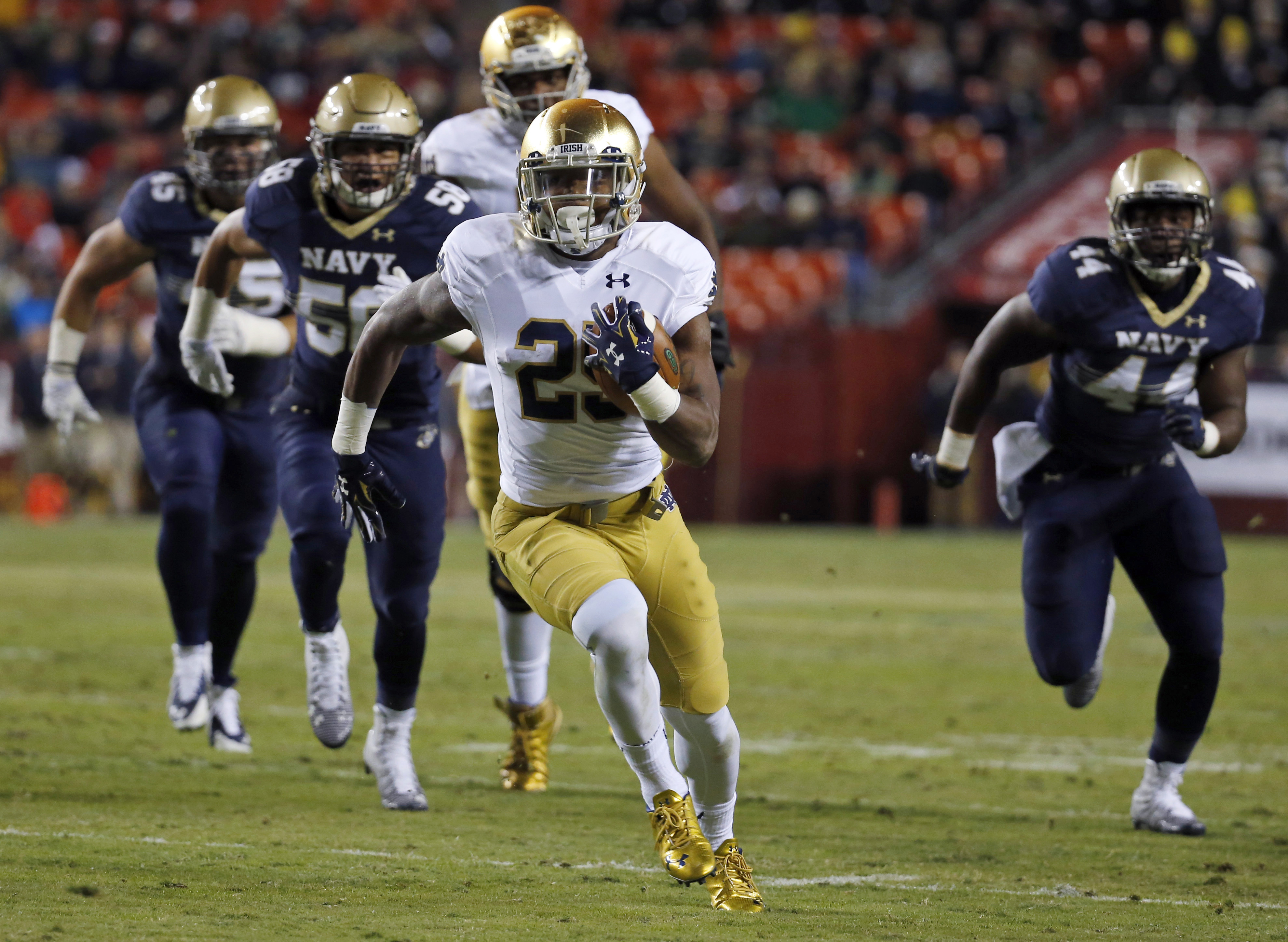 FILE - In this Nov. 1, 2014, file photo, Notre Dame running back Tarean Folston (25) runs with the ball as he is pursued by Navy linebackers Daniel Gonzales (58) and Obi Uzoma (44) during an NCAA college football game in Landover, Md. Folston tore the ACL