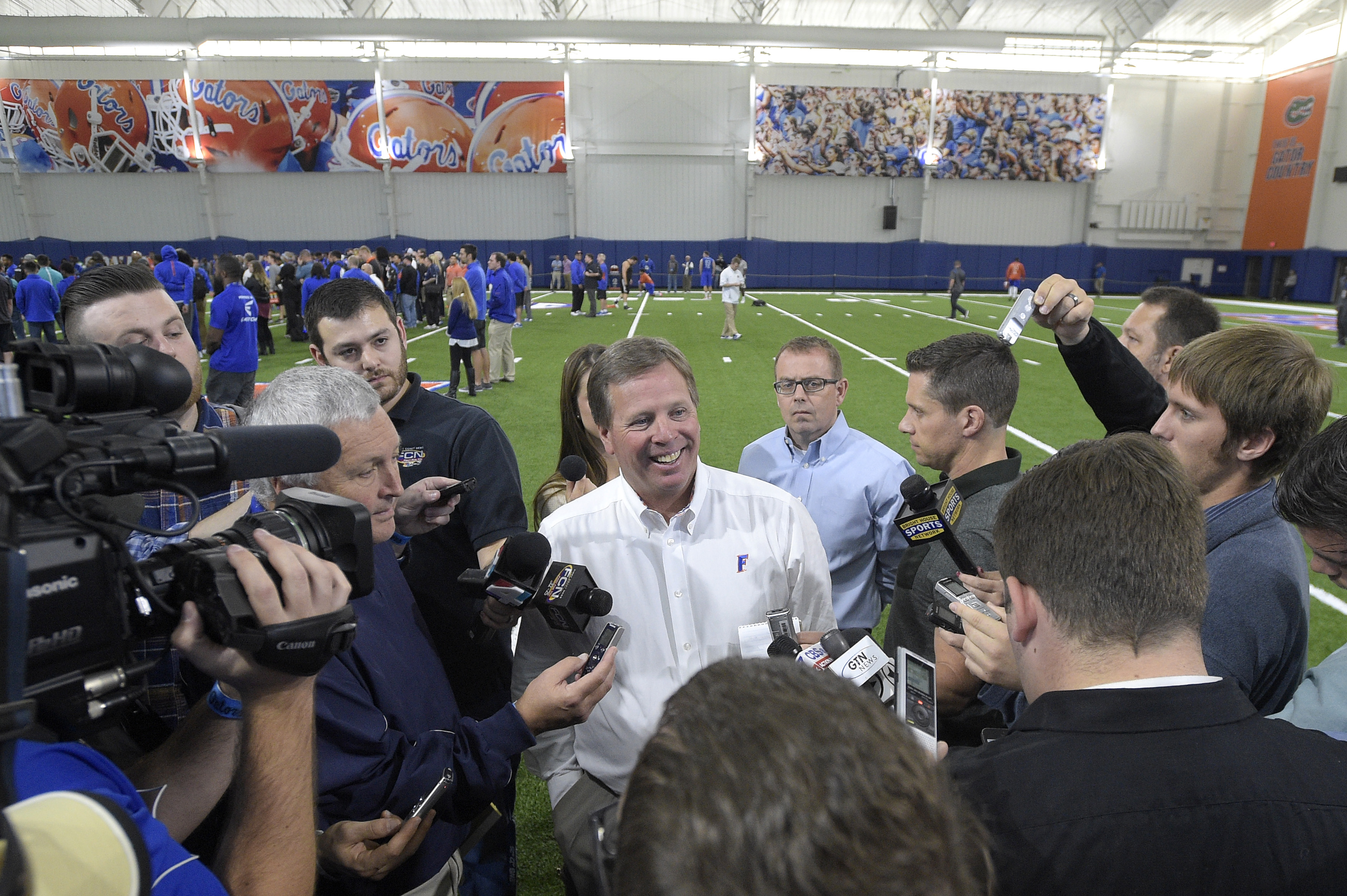 Florida head football coach Jim McElwain, center, answers questions from reporters during Florida's NFL Pro Day in Gainesville, Fla., Tuesday, March 22, 2016. (AP Photo/Phelan M. Ebenhack)