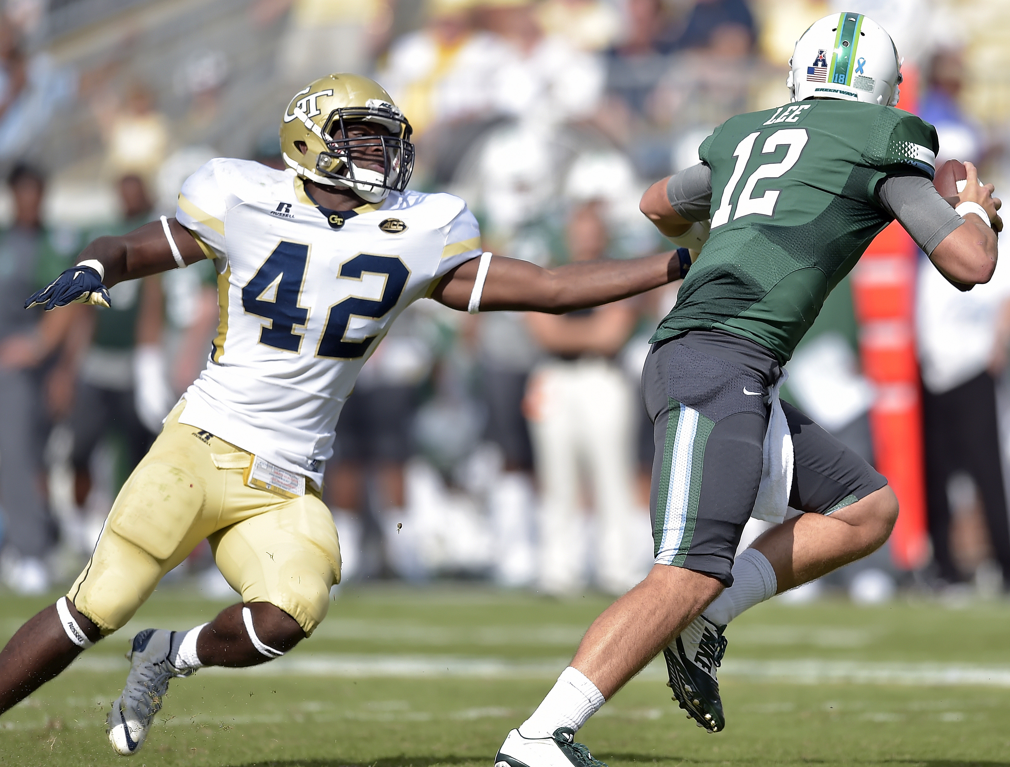 FILE - In this Sept. 12, 2015, file photo, Tulane quarterback Tanner Lee (12) runs out of the pocket as Georgia Tech defensive end KeShun Freeman (42) rushes in during the first half of an NCAA college football game in Atlanta. Freeman returns as third-ye