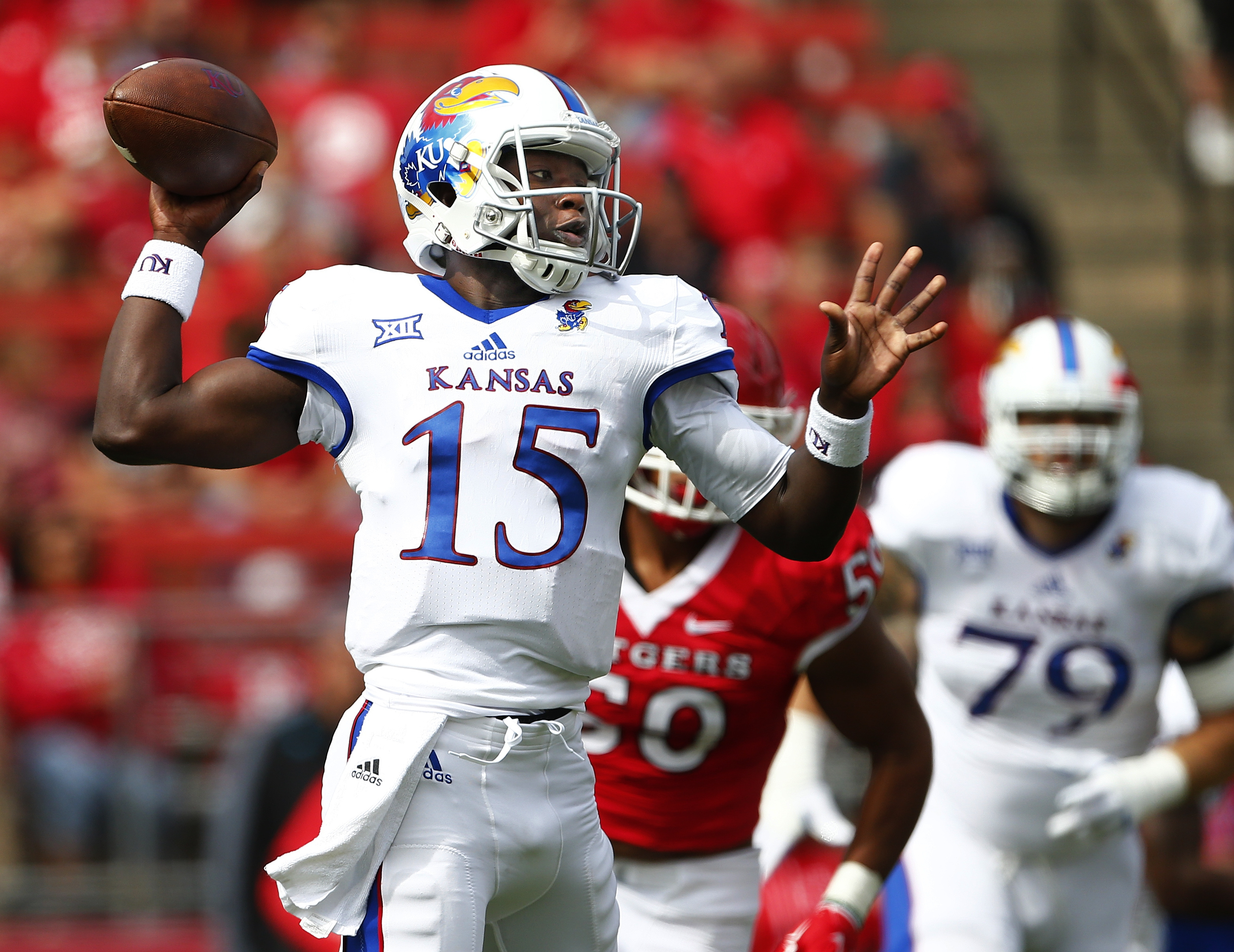 FILE - In this Sept. 26, 2015, file photo, Kansas quarterback Deondre Ford (15) throws a pass against Rutgers during the first quarter of an NCAA college football game in Piscataway, N.J. Kansas quarterbacks Montell Cozart and Deondre Ford were granted ha