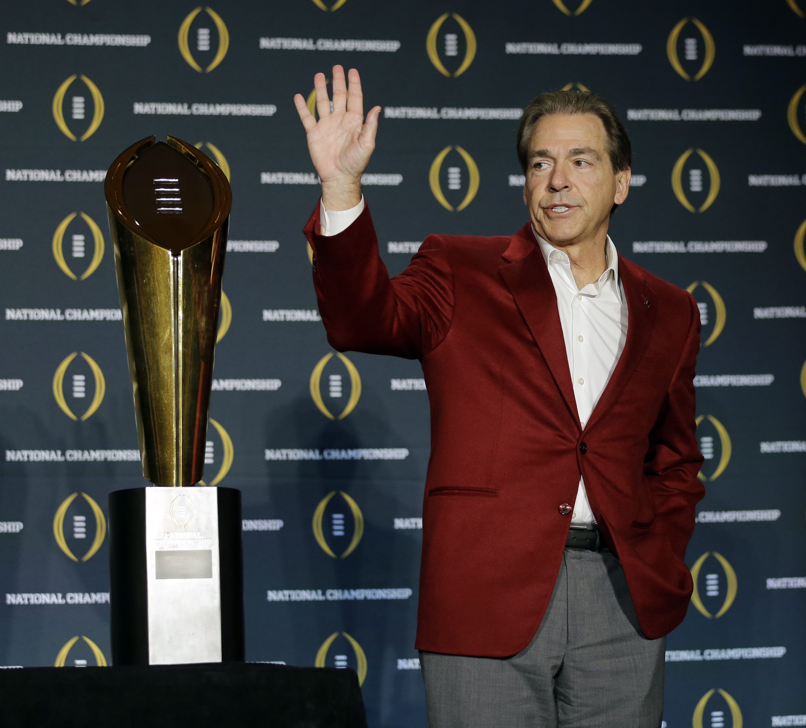 Alabama head coach Nick Saban poses with the championship trophy during a news conference for the NCAA college football playoff championship Tuesday, Jan. 12, 2016, in Scottsdale, Ariz. Alabama beat Clemson 45-40 to win the championship. (AP Photo/David J