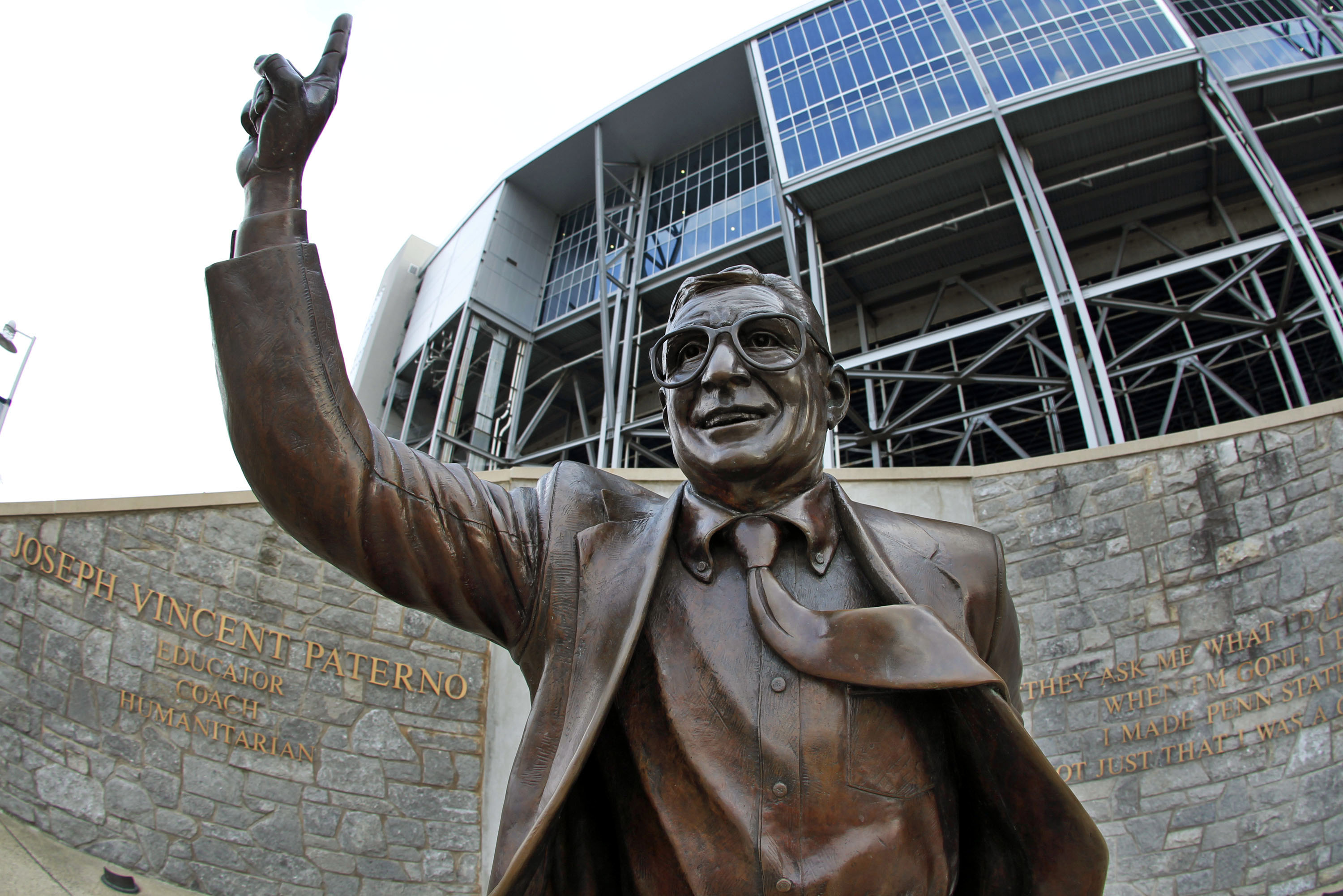 This photo taken with a fisheye lens shows a statue of former Penn State Football coach Joe Paterno stands outside Beaver Stadium on the Penn State campus Wedneday, July 11, 2012. (AP Photo/Gene J. Puskar)