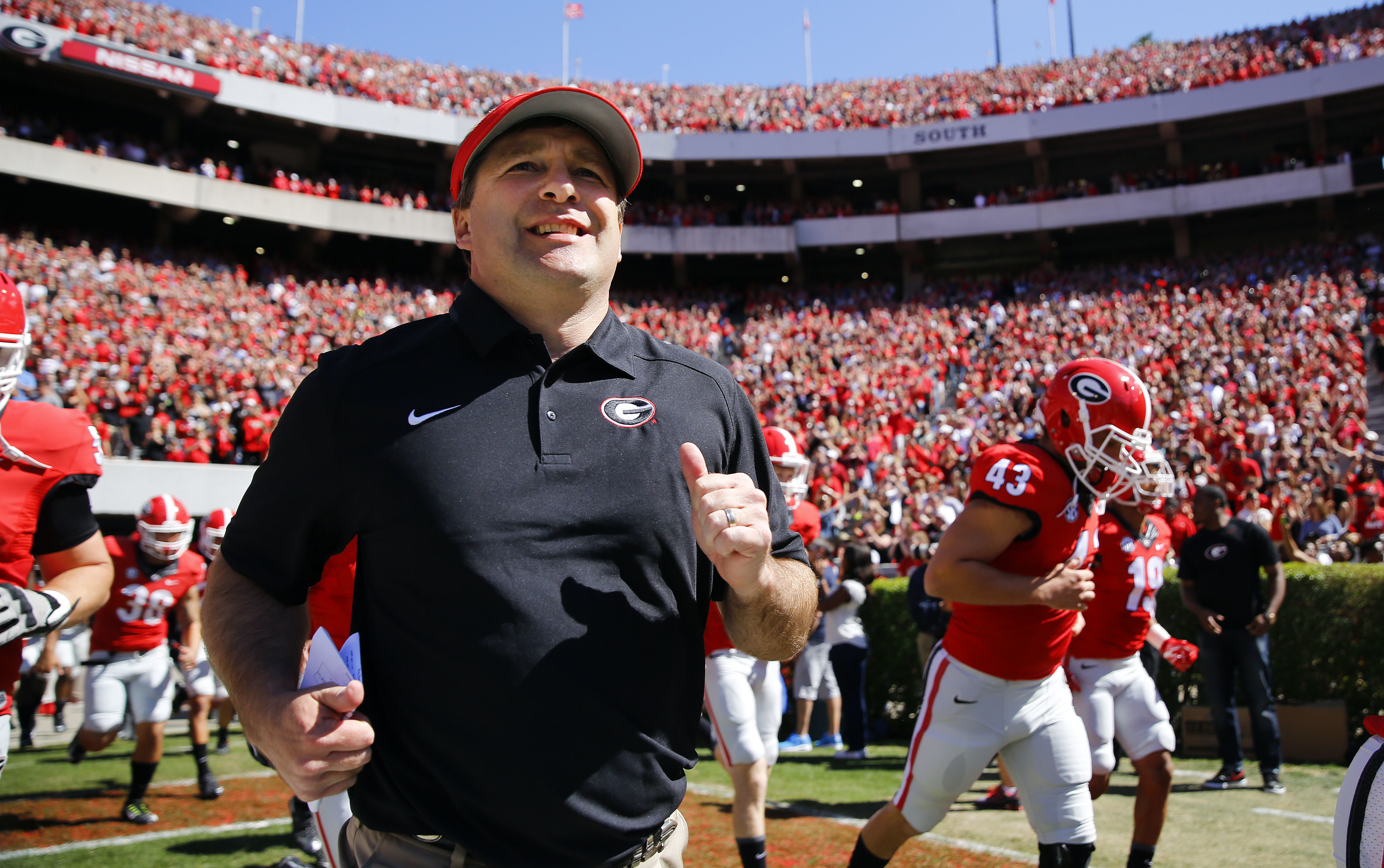 FILE - In this April 16, 2016 file photo, Georgia first-year head coach Kirby Smart runs into a packed Sandford Stadium with his players for the school's spring NCAA college football game in Athens, Ga. The Southeastern Conference Eastern Divisions new lo
