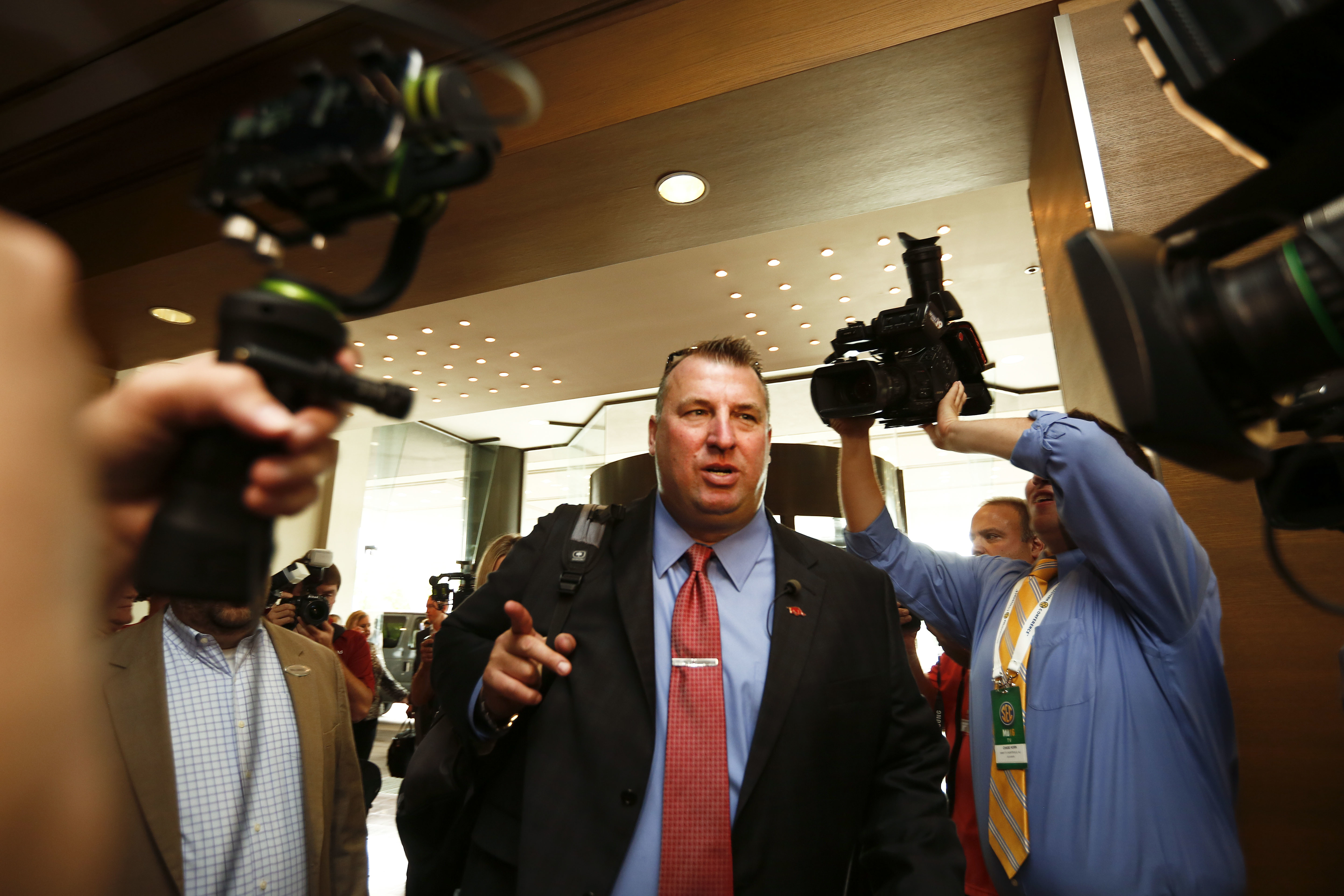 Arkansas coach Bret Bielema walks into a sea of media at the Southeastern Conference NCAA college football media days, Wednesday, July 13, 2016, in Hoover, Ala. (AP Photo/Brynn Anderson)