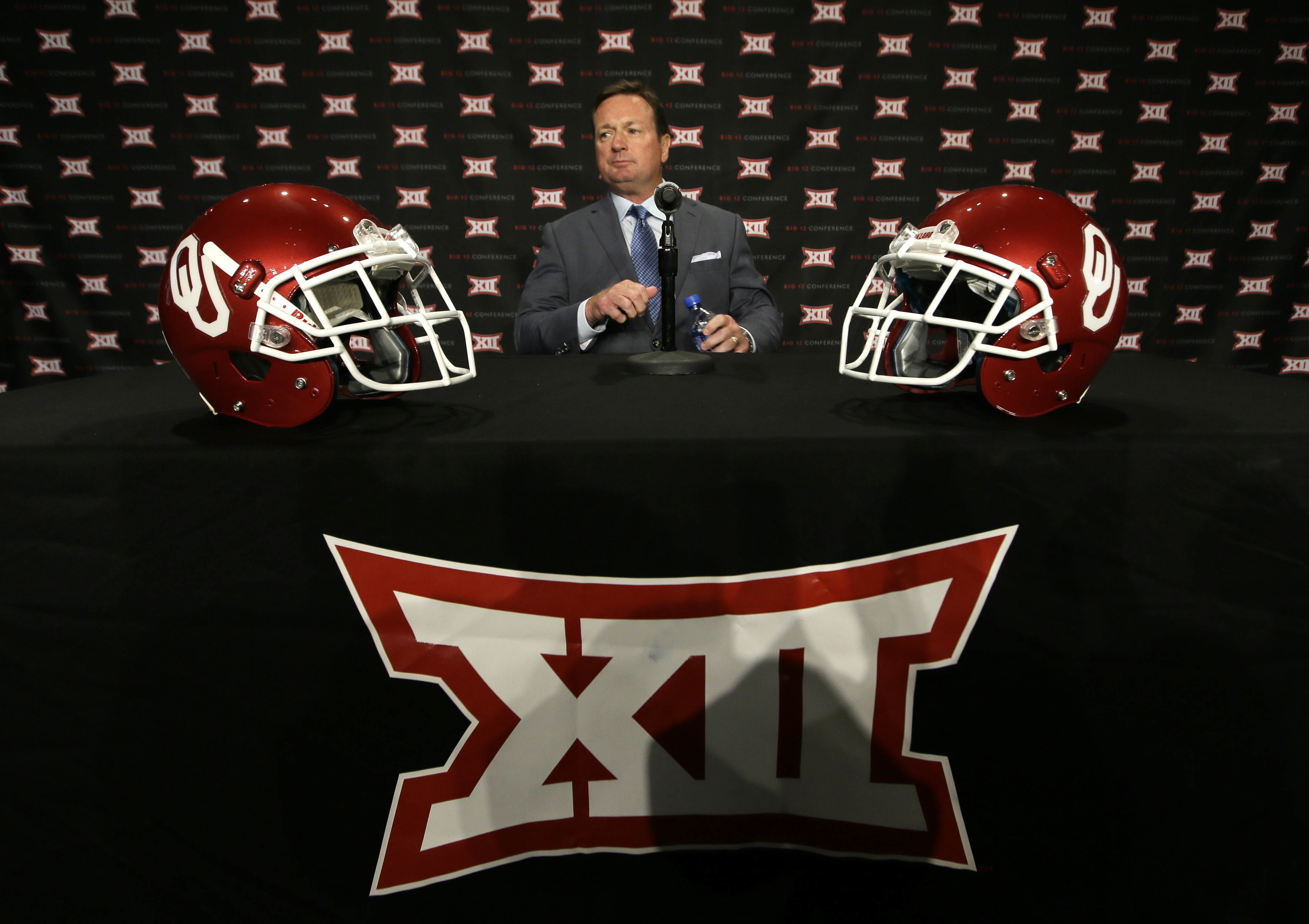 CORRECTS THE COACHES NAME TO BOB STOOPS, AND NOT MIKE GUNDY AS ORIGINALLY SENT - Oklahoma head coach Bob Stoops takes a seat to speak to reporters during the Big 12 college football media days in Dallas, Tuesday, July 19, 2016. (AP Photo/LM Otero)