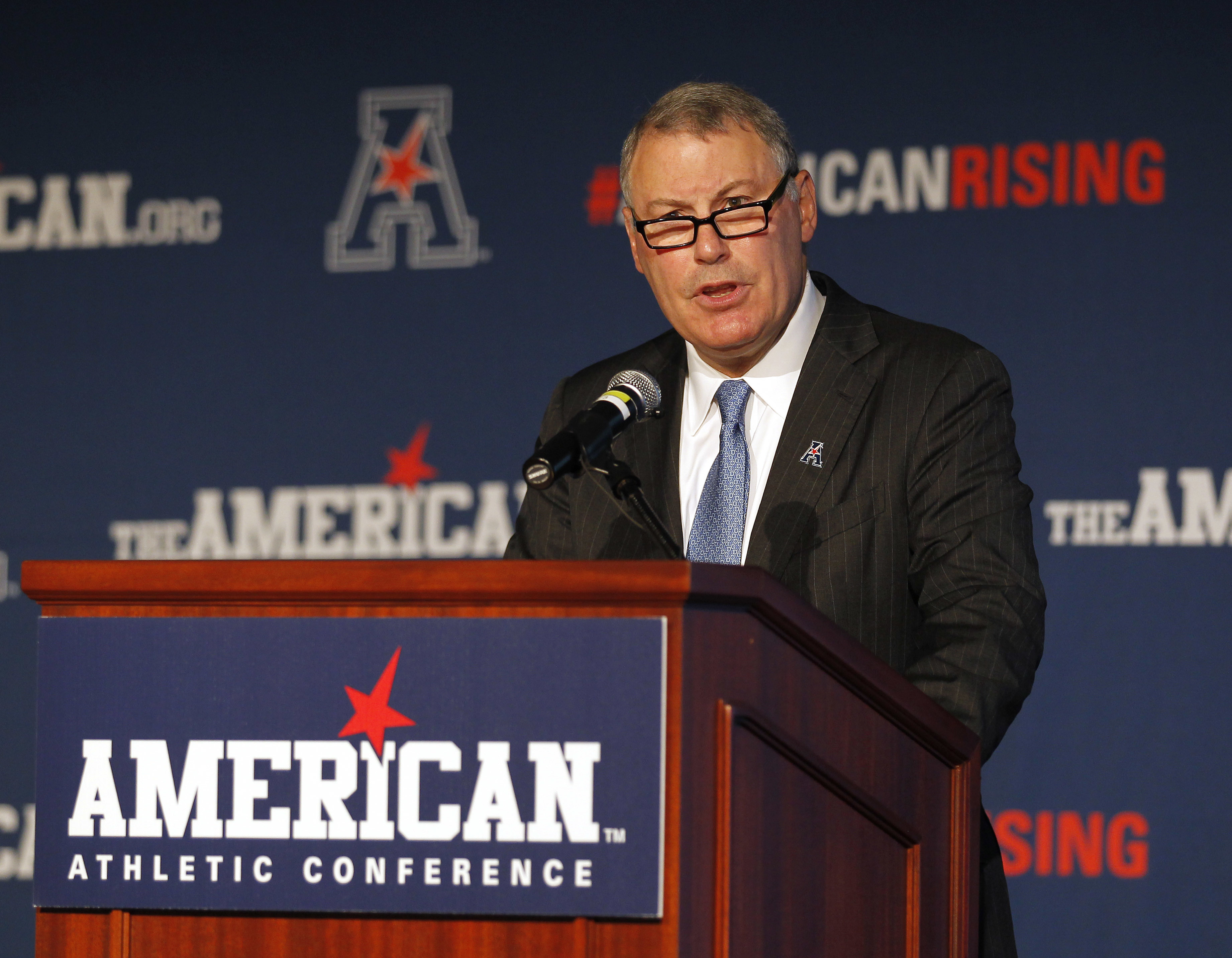 FILE - In this Aug. 4, 2015, file photo, American Athletic Conference Commissioner Mike Aresco addresses the media during an NCAA football media day in Newport, R.I. The AAC gathers for its media day, but hanging over the start of the season is Big 12 exp