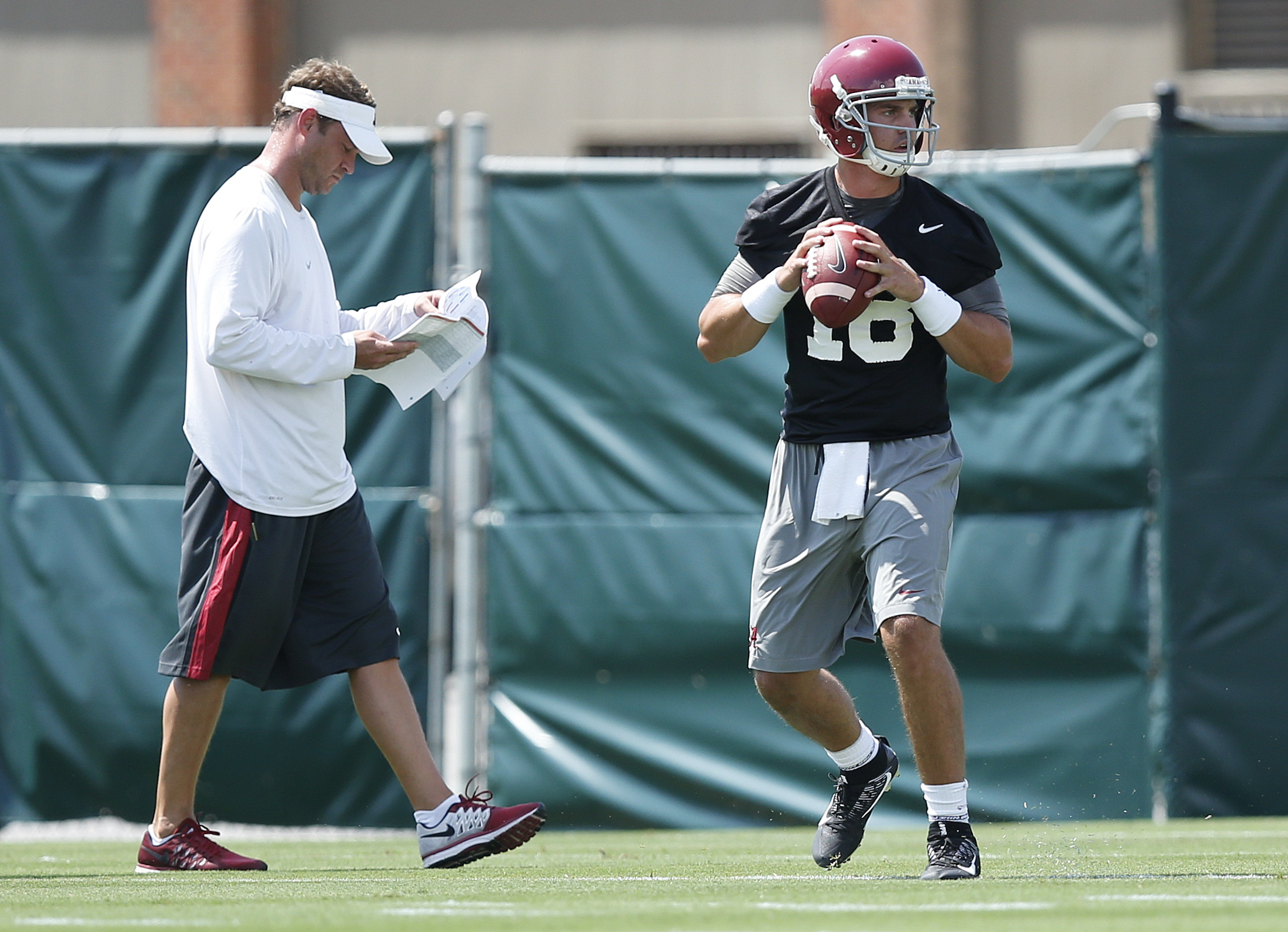 Alabama offensive coordinator Lane Kiffin walks behind quarterback Cooper Bateman as he sets back to pass during a drill at an NCAA college football practice, Thursday, Aug. 4, 2016, in Tuscaloosa, Ala. (AP Photo/Brynn Anderson)