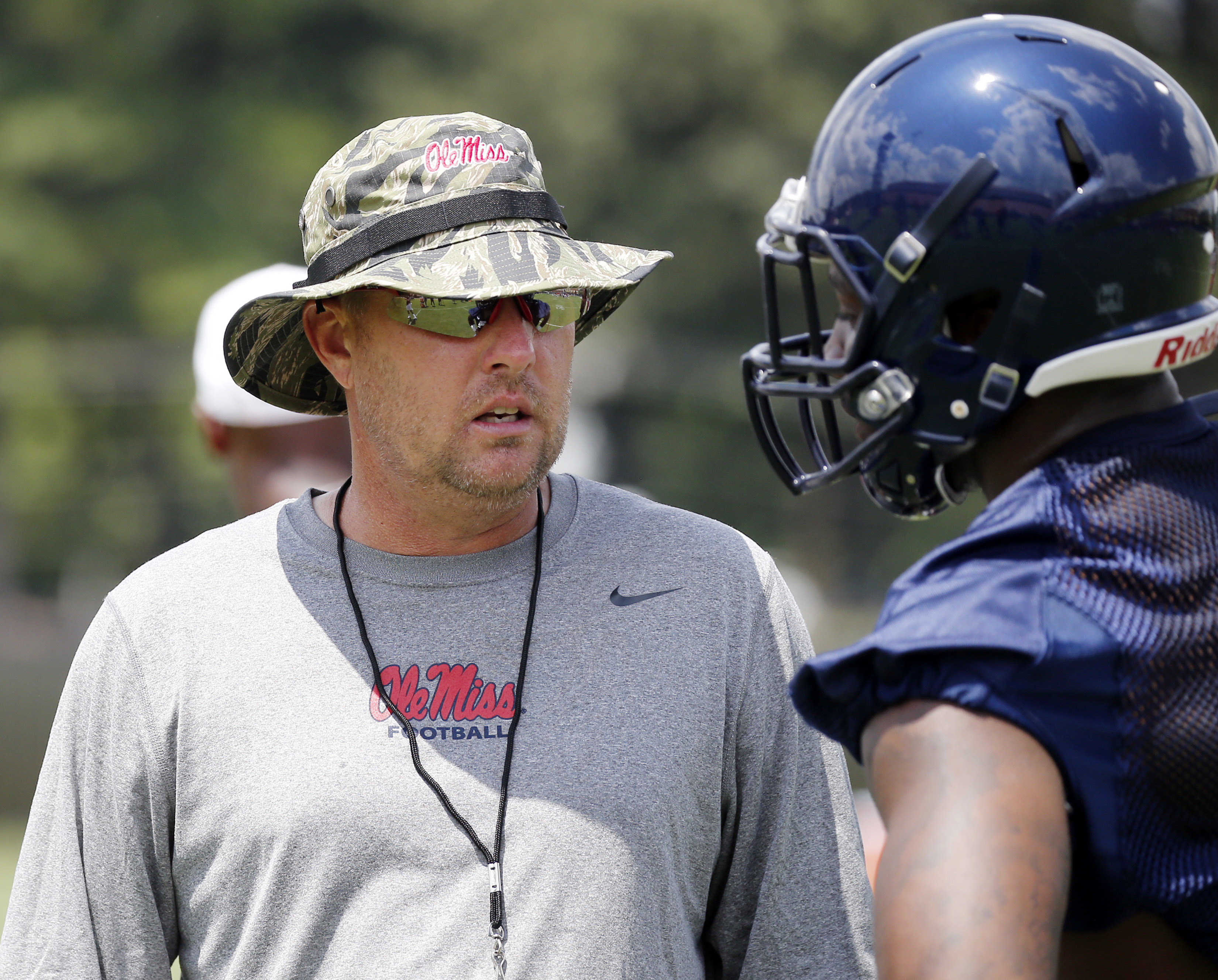 Mississippi football coach Hugh Freeze speaks with a player during an NCAA college football practice prior to media day activities, Monday, Aug. 8, 2016, in Oxford, Miss. (AP Photo/Rogelio V. Solis)