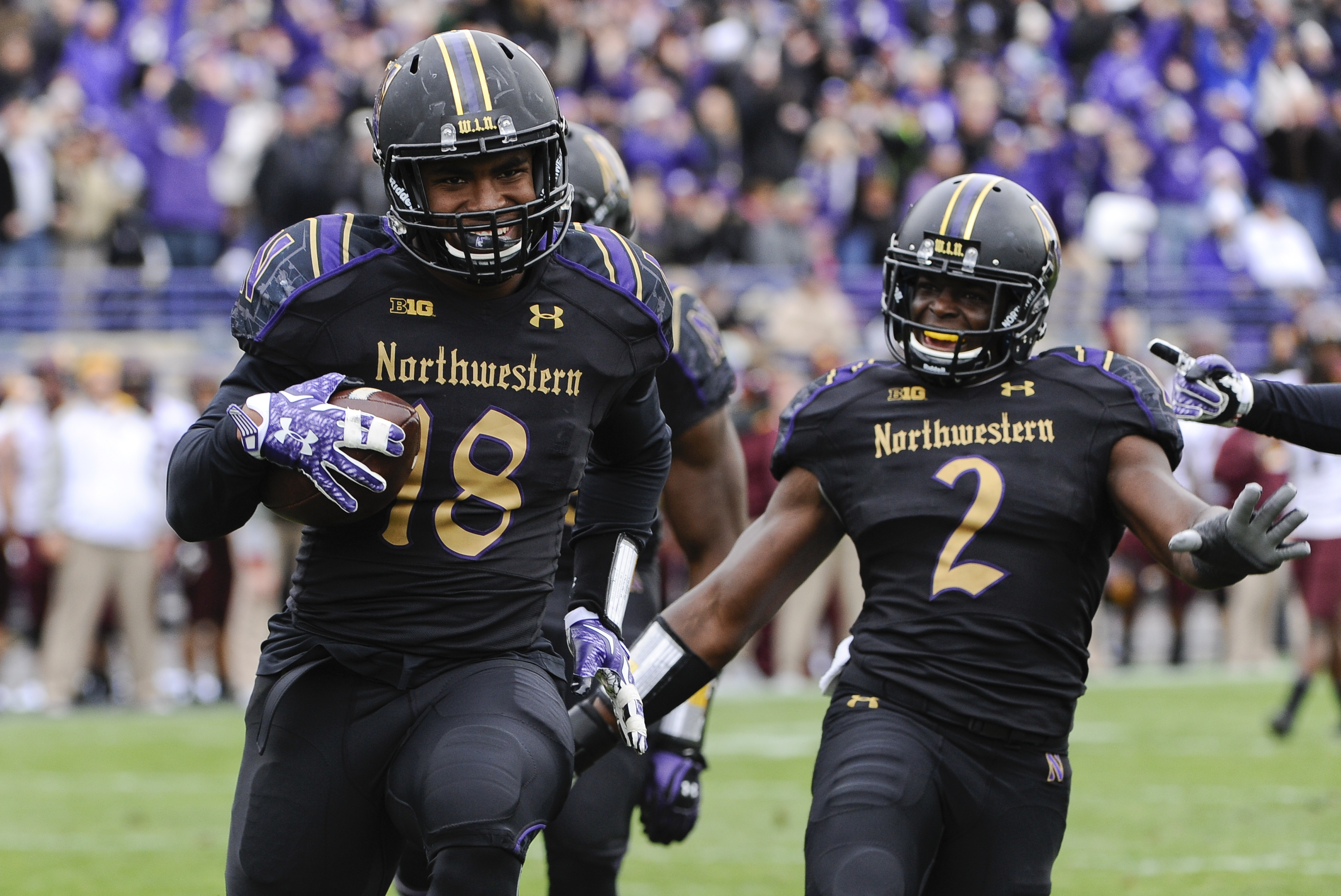 FILE - In this Oct. 3, 2015, file photo, Northwestern linebacker Anthony Walker (18) runs for a touchdown after picking up a Minnesota fumble as teammate safety Traveon Henry (2) watches during an NCAA college football game in Evanston, Ill. The star line
