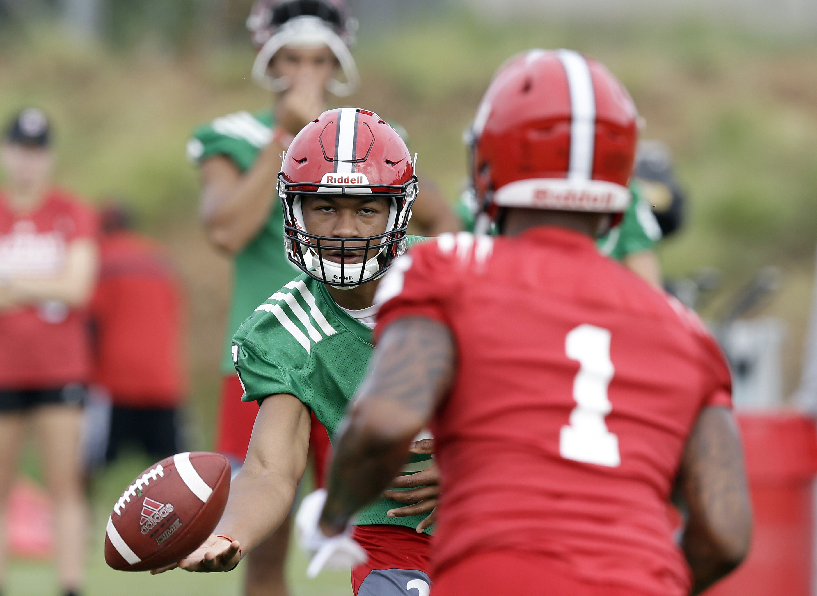 In this photo taken Monday, Aug. 1, 2016 North Carolina State quarterback Jalan McClendon tosses the ball to Jaylen Samuels (1) during an NCAA college football practice in Raleigh, N.C. (AP Photo/Gerry Broome)