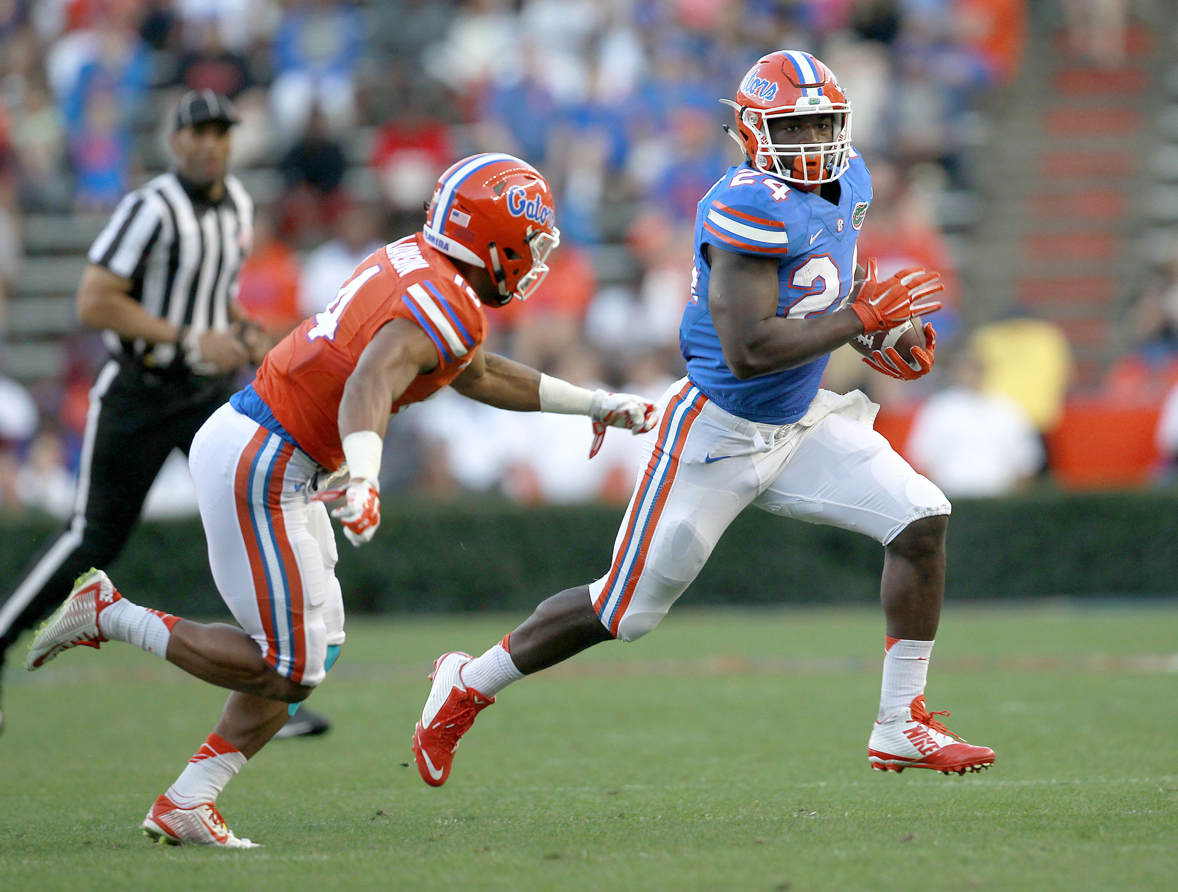 FILE - In this April 8, 2016, file photo, Florida running back Mark Thompson runs upfield past defensive back Chris Williamson during a spring NCAA college football game in Gainesville, Fla. The junior college transfer wants to have 1,000 yards rushing th