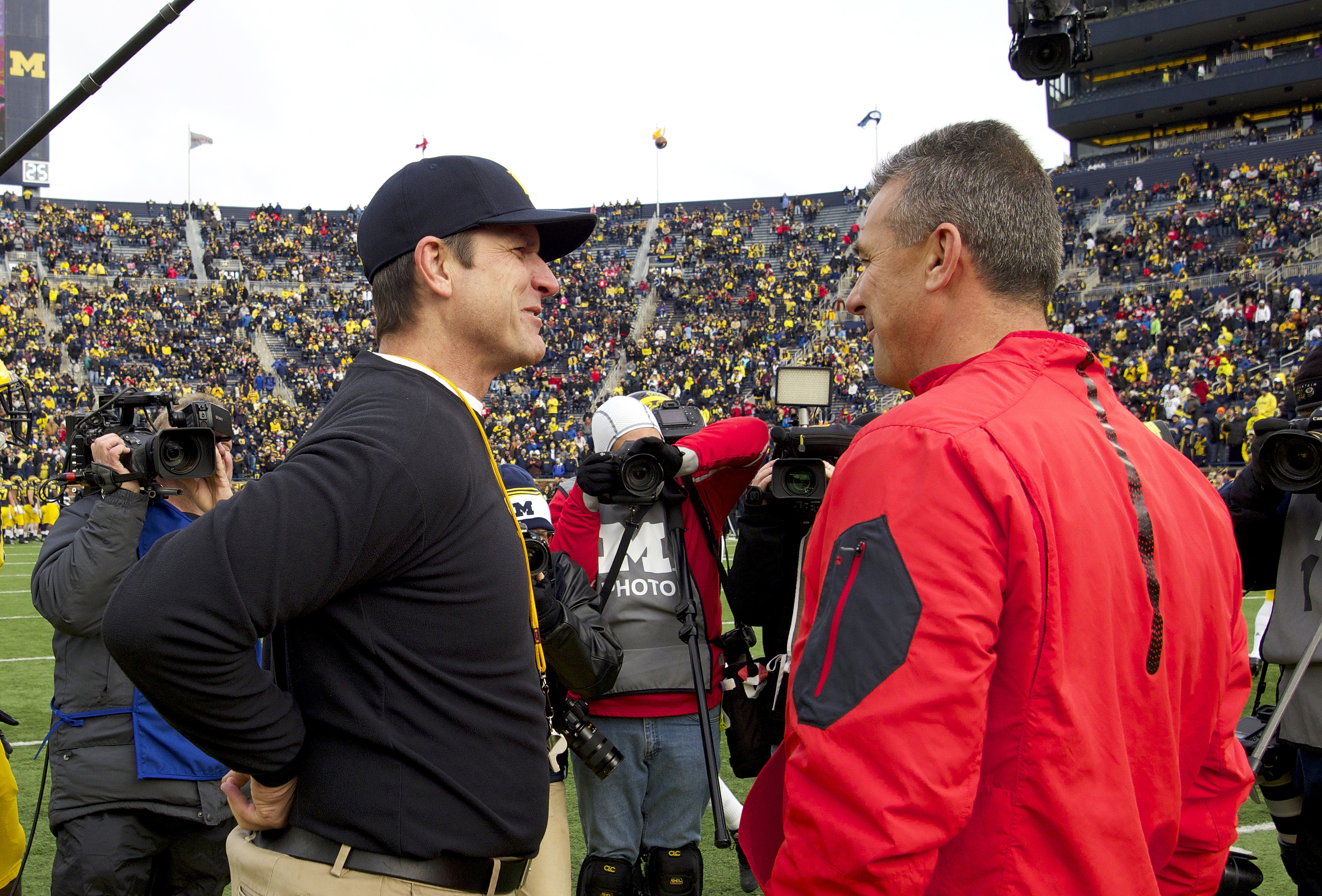FILE - In this Nov. 27, 2015, file photo, Michigan head coach Jim Harbaugh, left, greets Ohio State head coach Urban Meyer, right, on the Michigan Stadium field before an NCAA college football game in Ann Arbor, Mich.Tthe second Harbaugh-Meyer matchup on